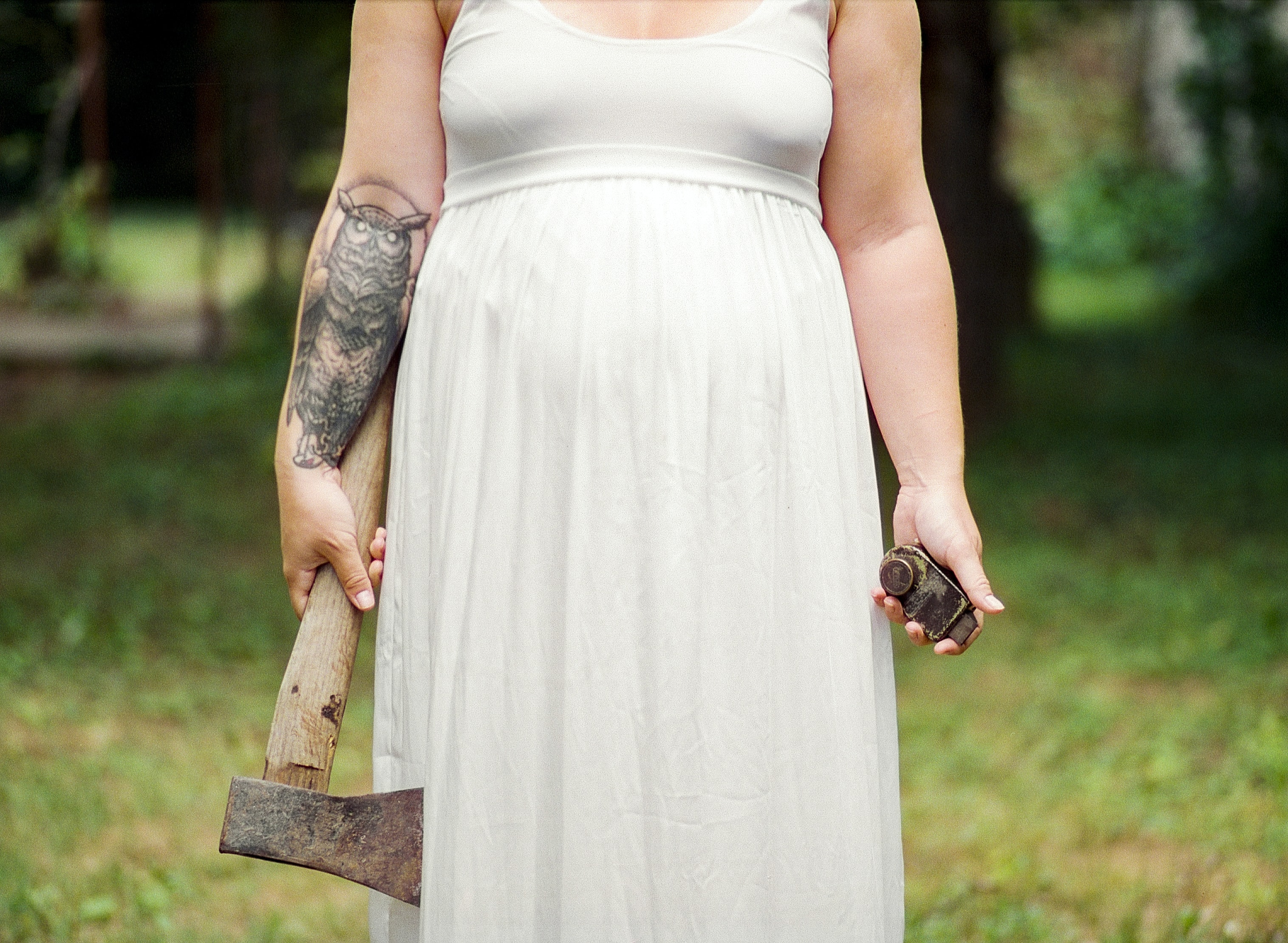 woman in white dress holding axe during daytime