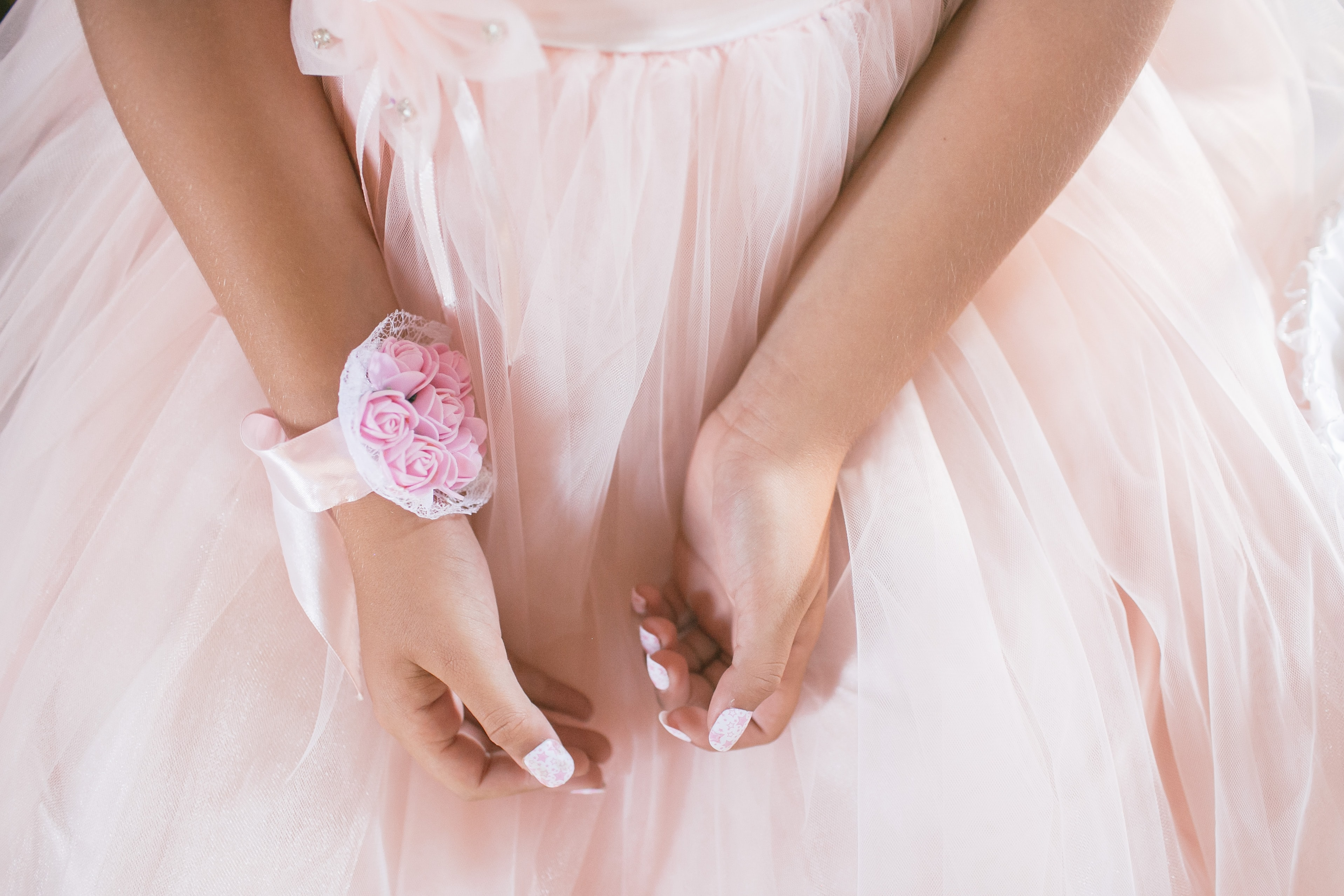 Close up of the hands of a little girl in a dress with a pink wrist corsage