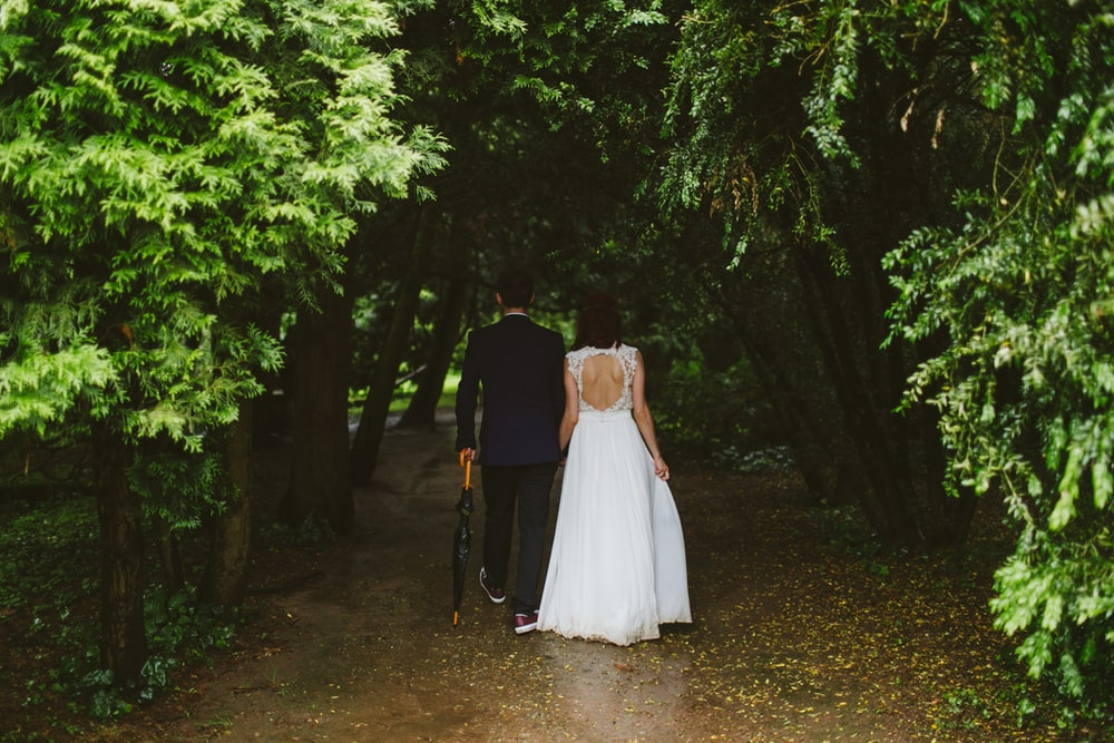 couple walking under green trees