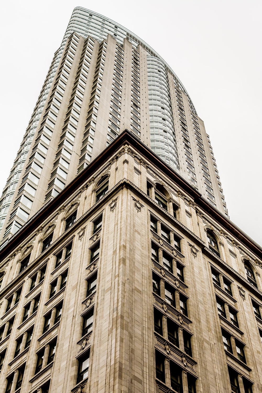 low angle photo of high rise building under gray sky