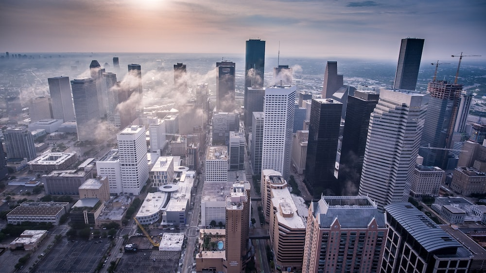 The drone view of a city with tall buildings and cloud line over it