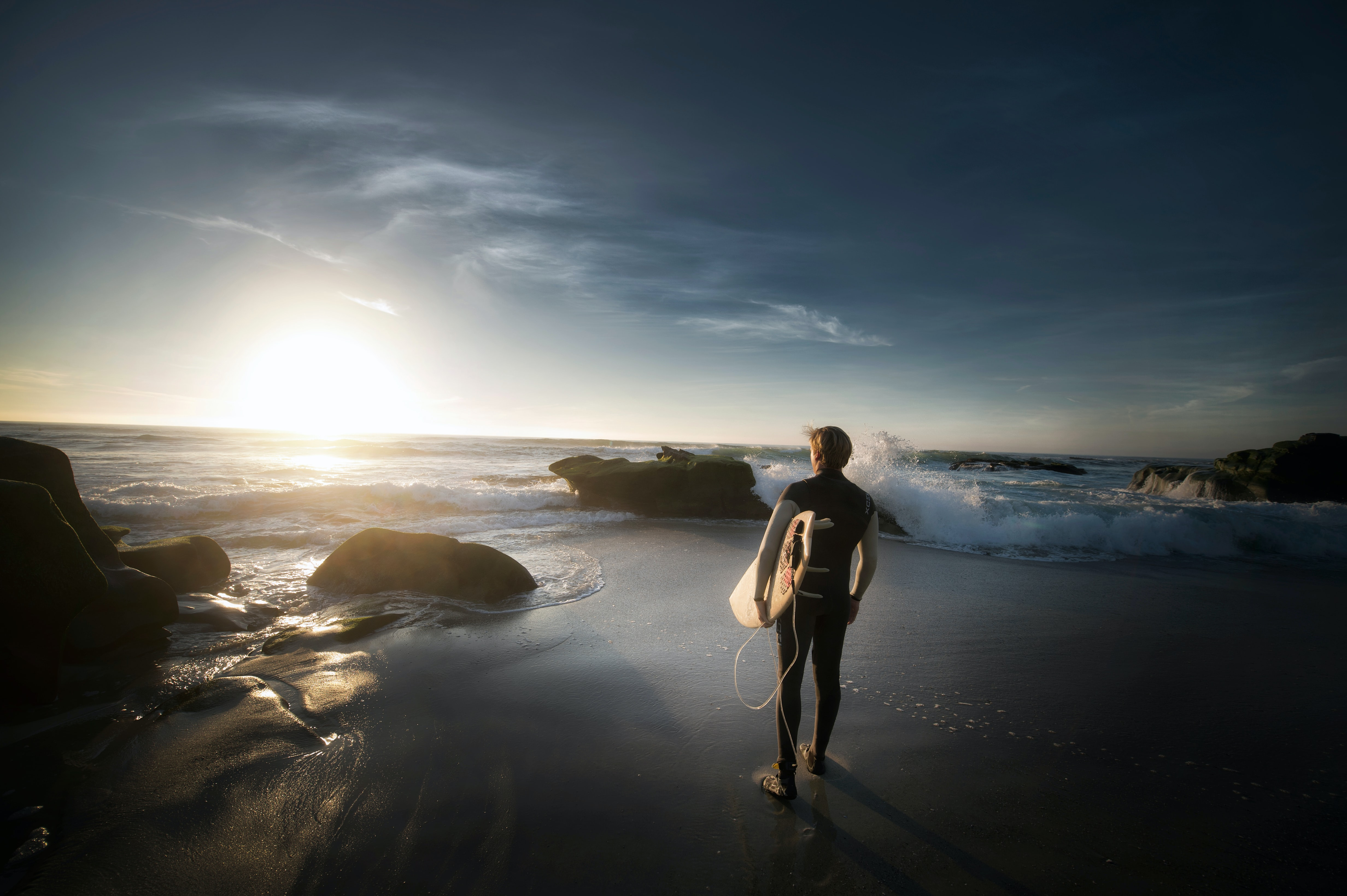 Surfer with surfboard in wetsuit standing on the wet sand beach looking at the sunset in San Diego