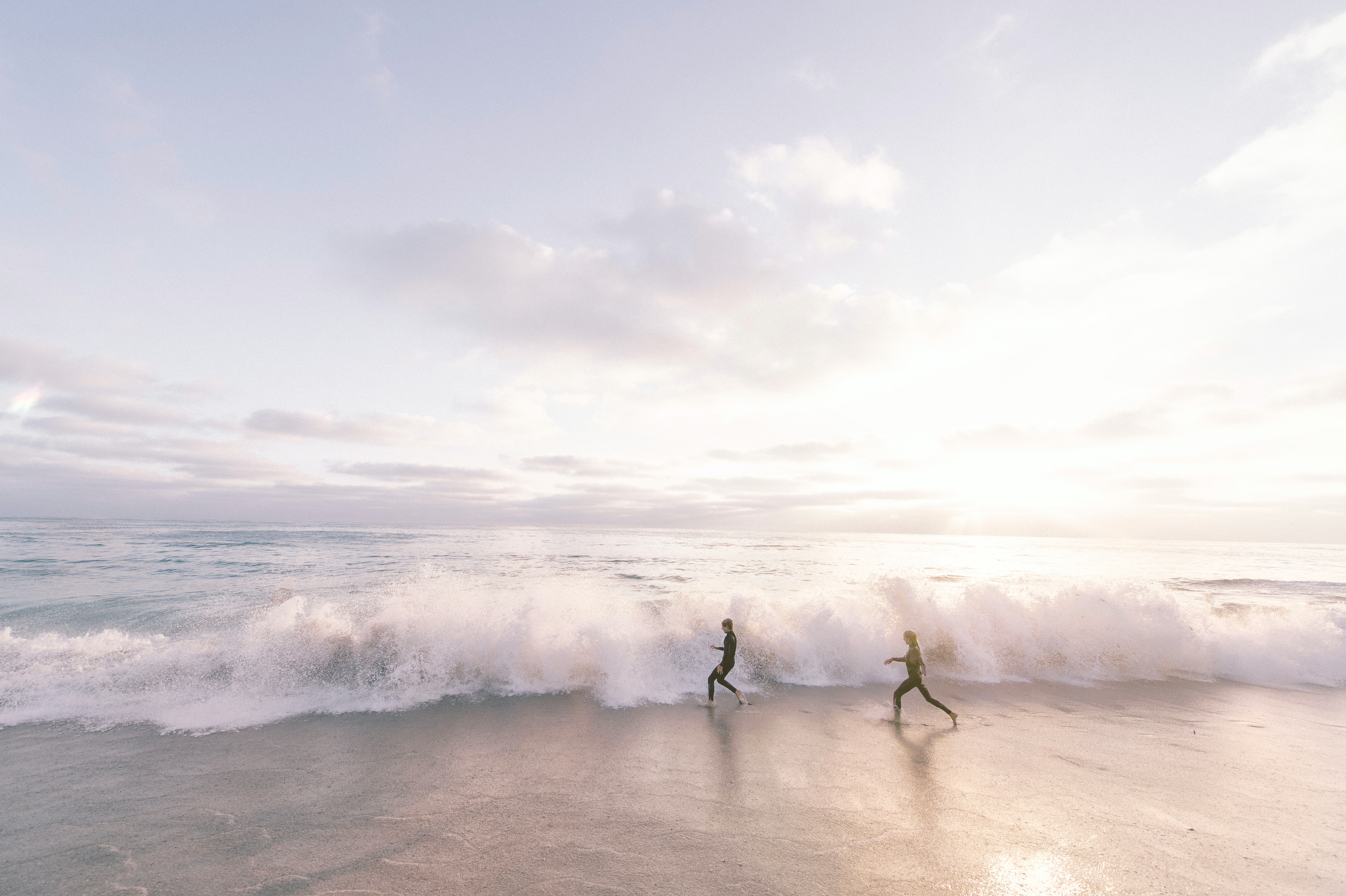 two person running on seaside beach during daytime