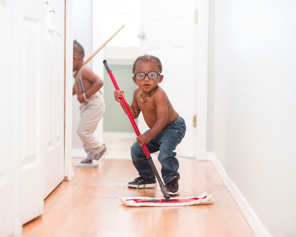 A funny African American Boy with glasses, using a push mop to clean the haul away.