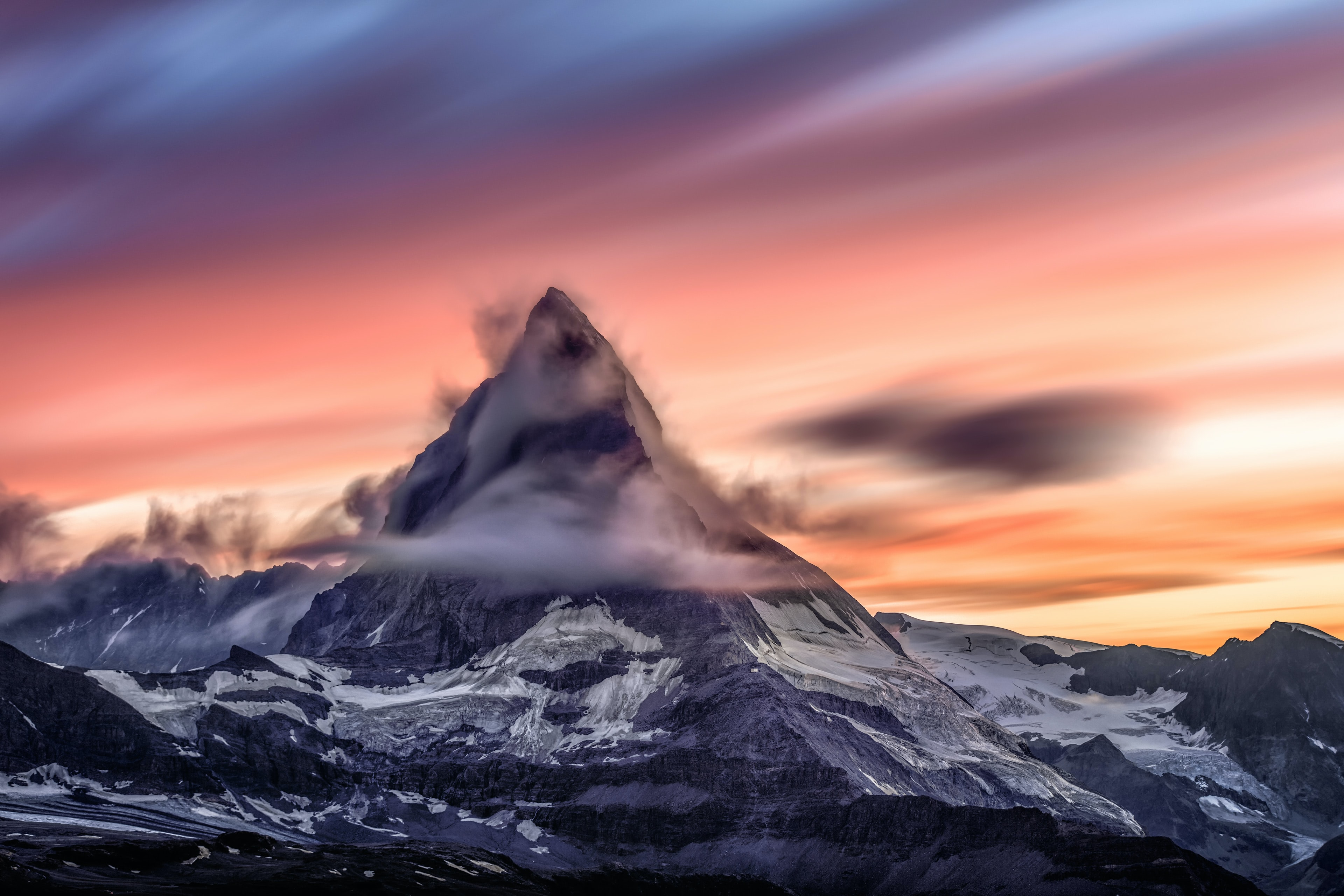 Snowcapped mountain peak on a cloudy sunrise in Matterhorn