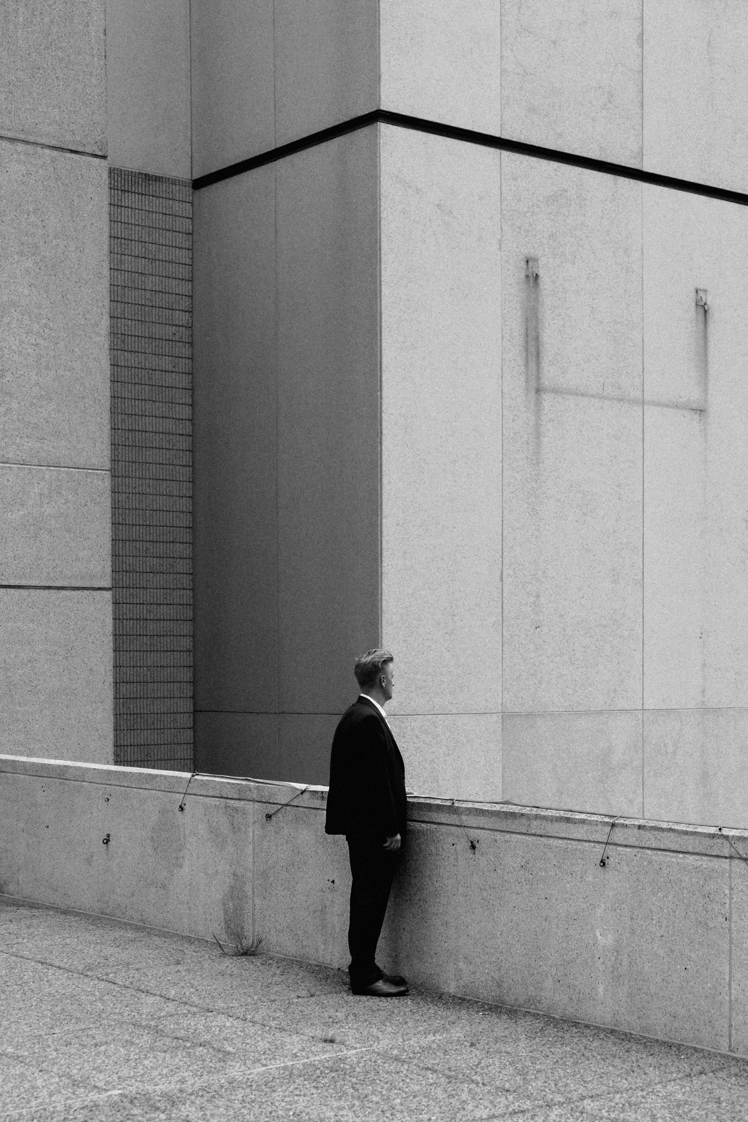 A black-and-white shot of a man in a black suit standing near a building ledge