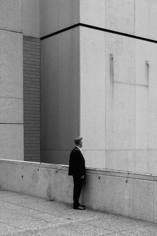 greyscale photo of man standing on bridge during daytime