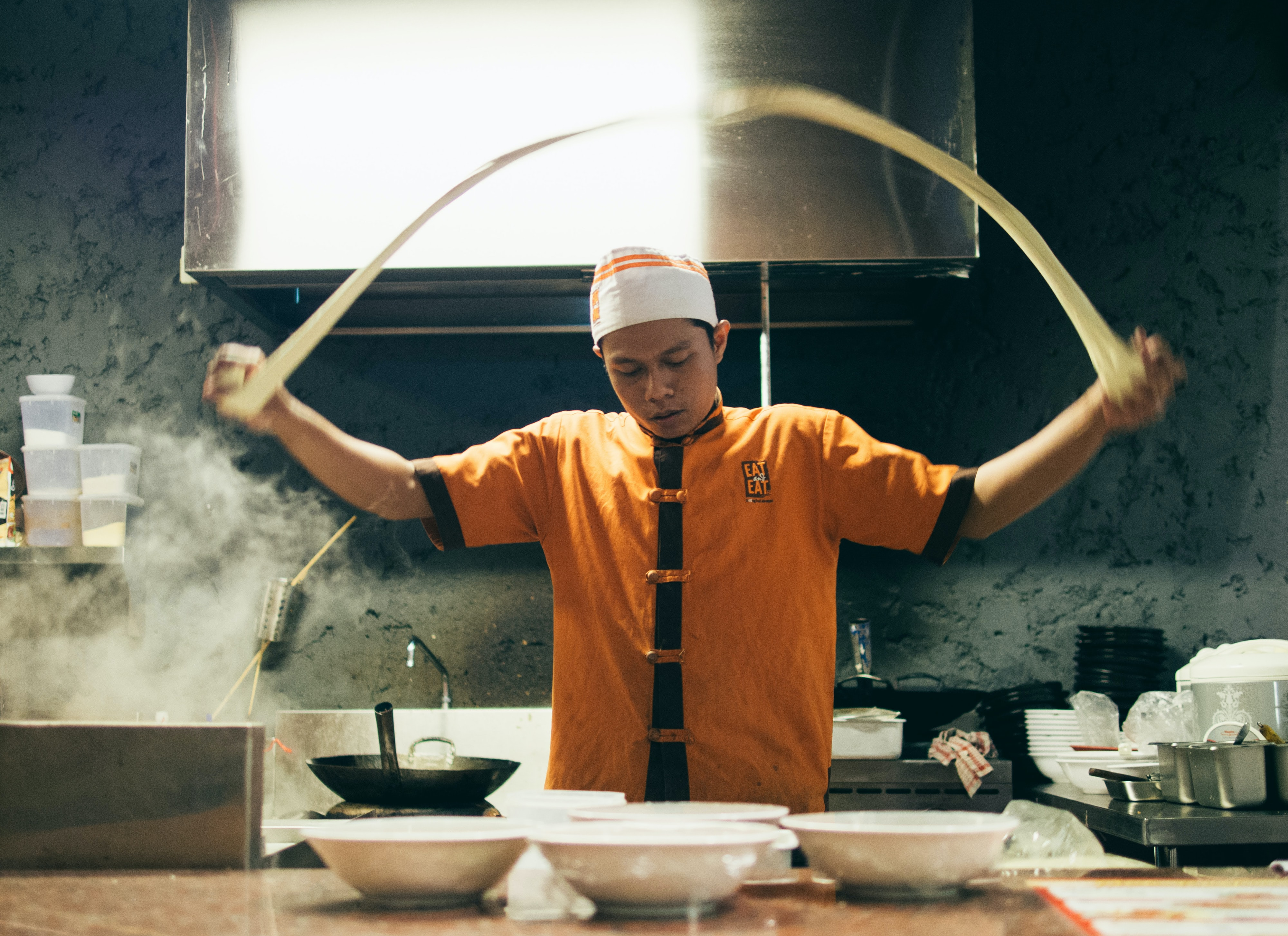A restaurant chef stretching dough in a kitchen
