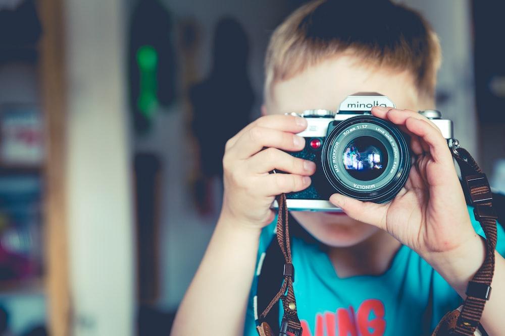 selective focus photography of boy holding gray Minolta bridge camera