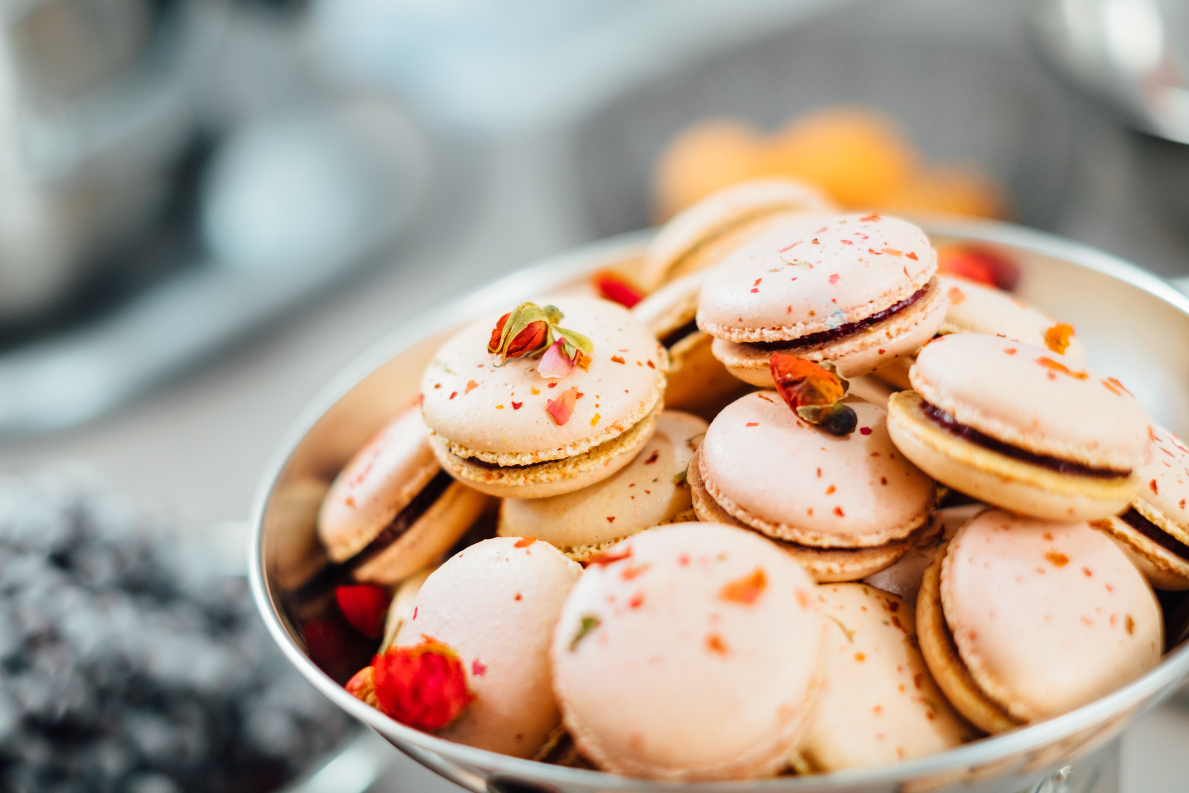 Dessert bowl of pink French macarons with rose petal garnish