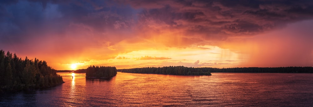 A Lake With An Island In Vaala Is Reflecting The Orange Sky During Sunset