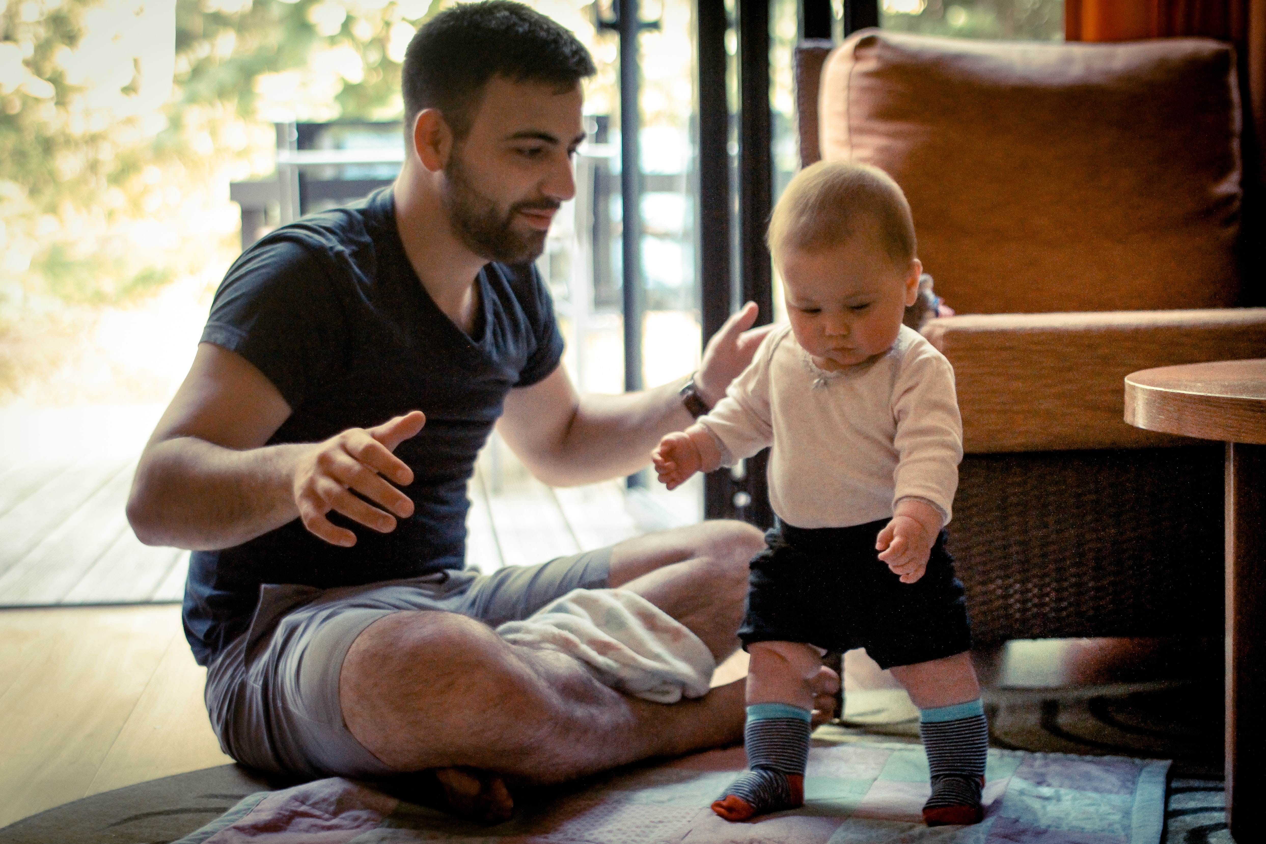 A man helping teach his 1 year old how to walk.