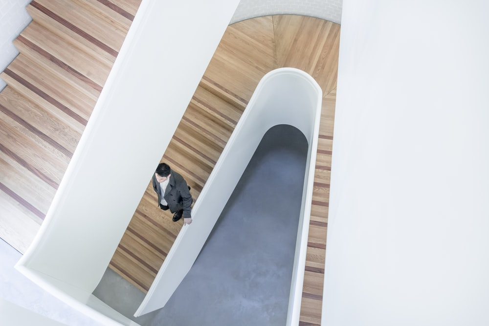 person stepping down on brown wooden stairs aerial photography