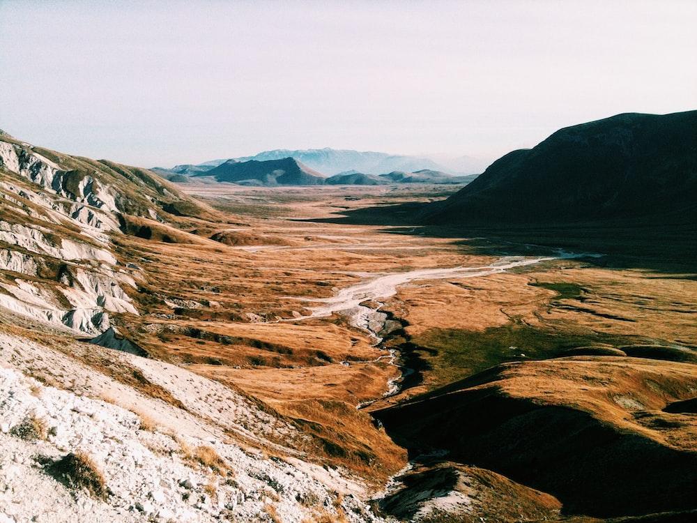 brown field near mountain range
