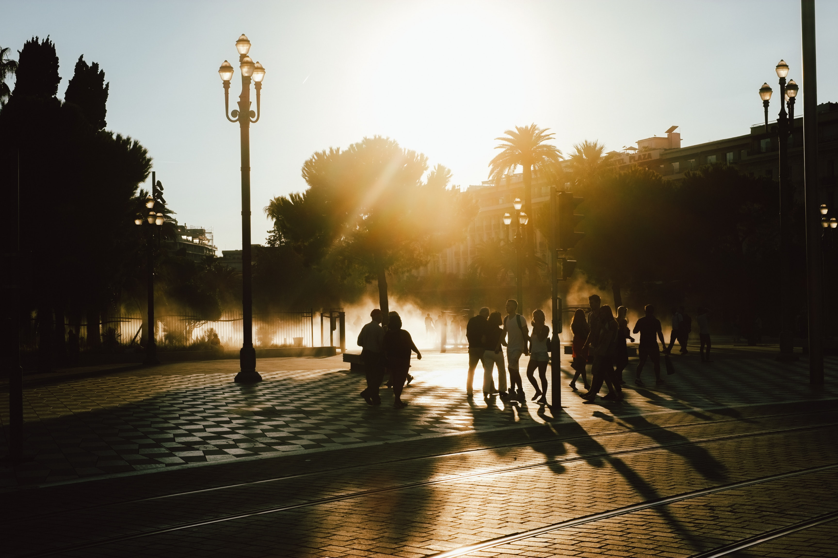 Silhouettes of pedestrians on the streets of Nice, as the sun sets behind palm trees in the distance