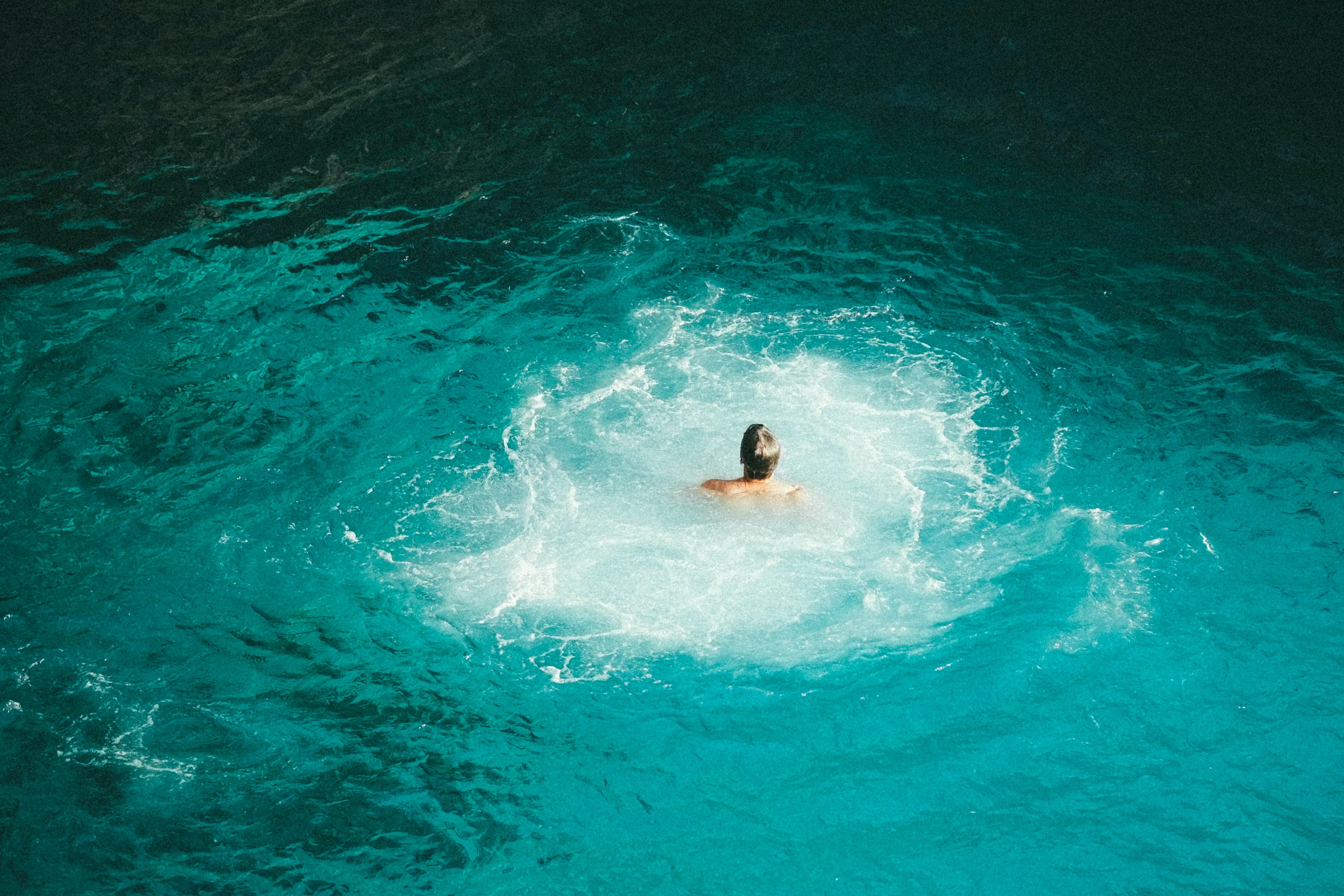 photo of person swimming on body of water