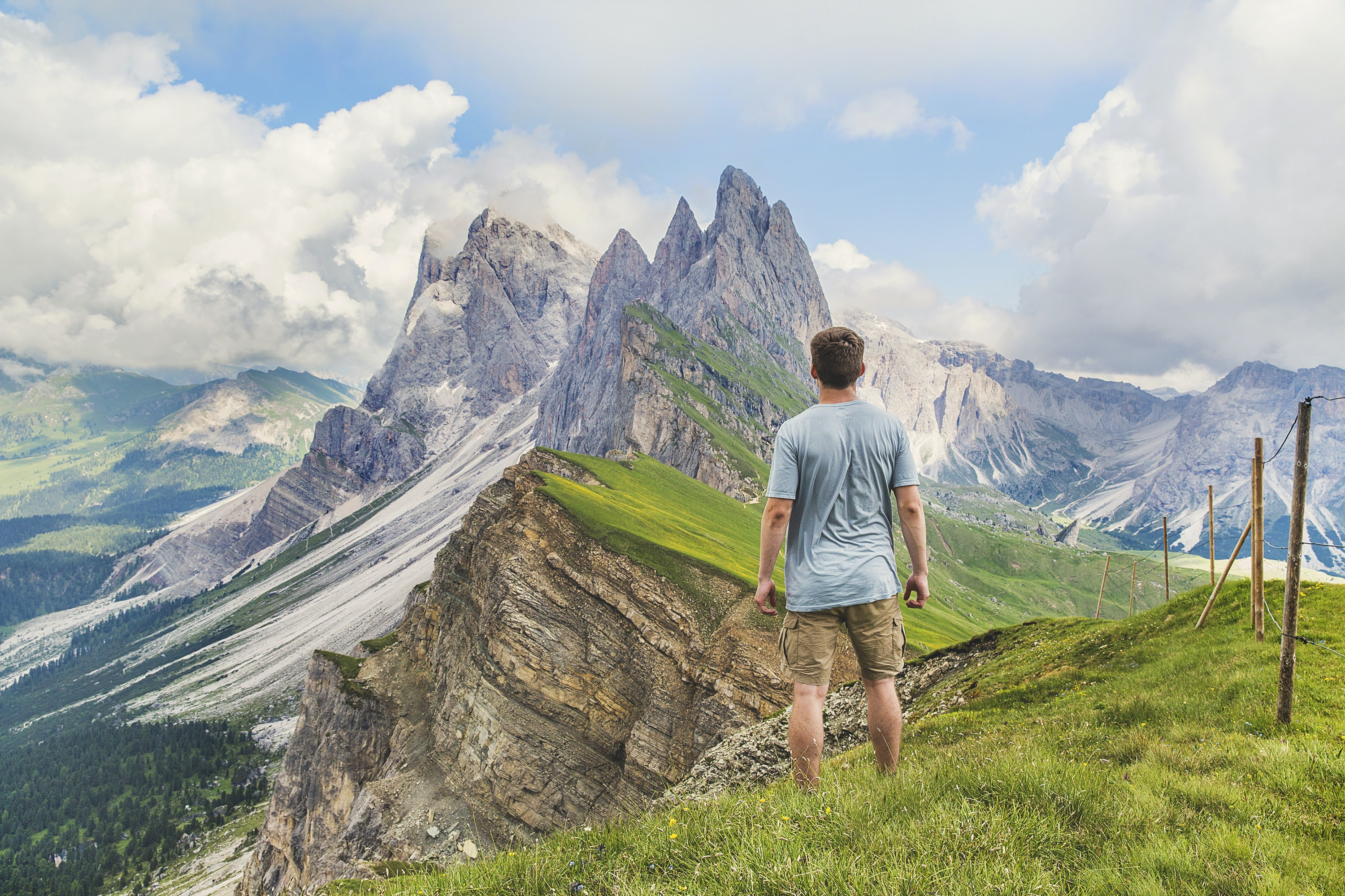 A man standing on a grass-covered ledge with view on craggy mountain peaks