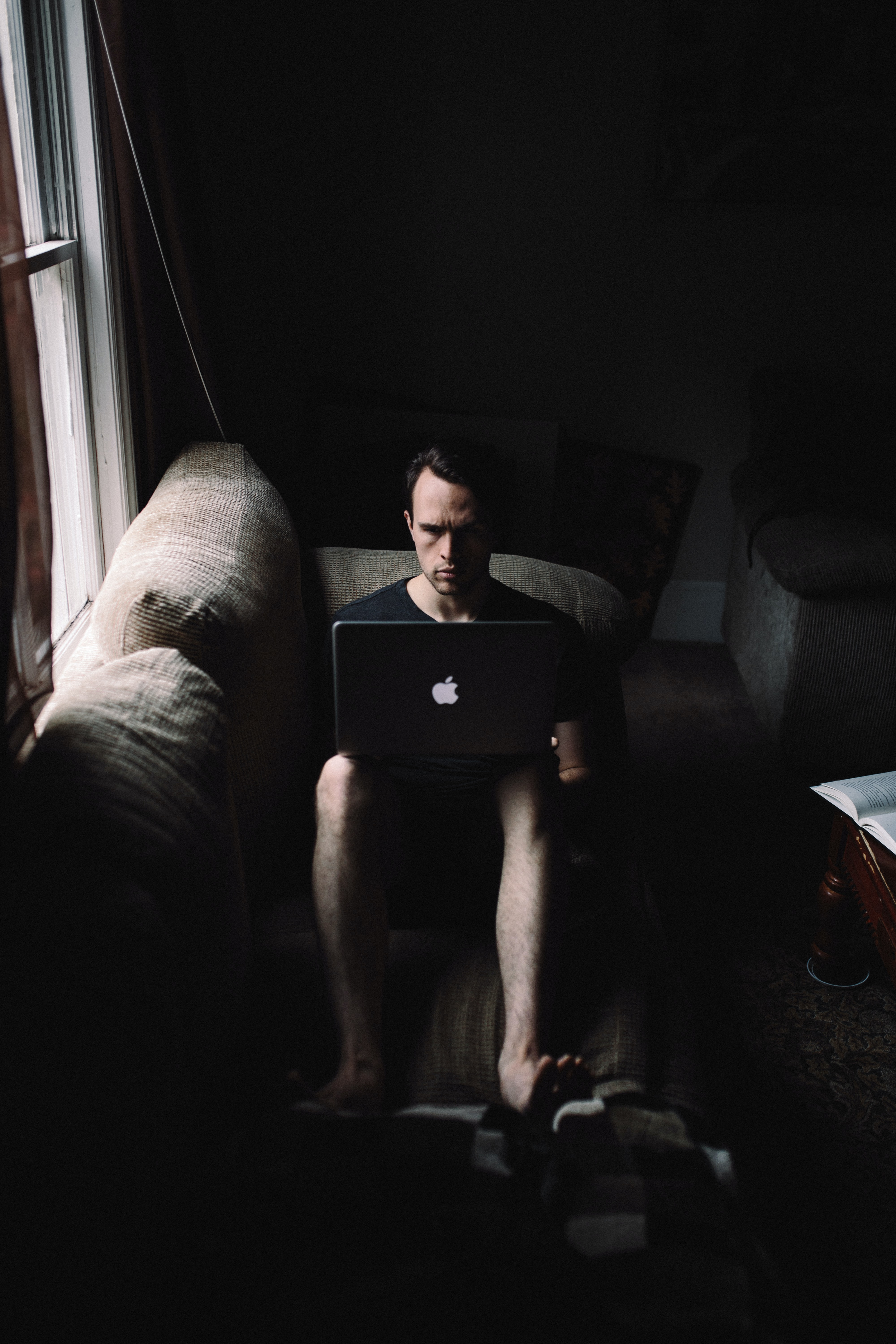 A barefoot man sitting on a sofa and looking at a MacBook on his lap