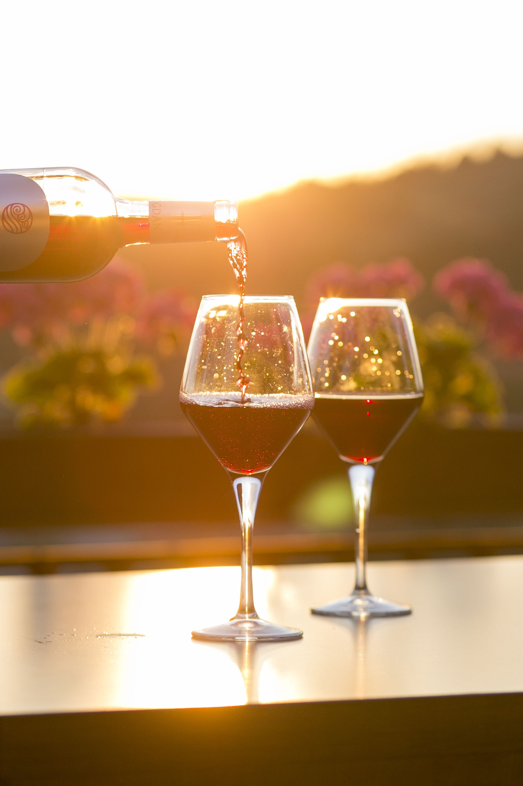 A person pouring red wine into one of two glasses with flowers and the setting sun in the background