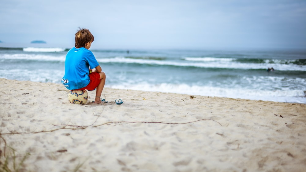 boy sitting on ball while staring at the ocean