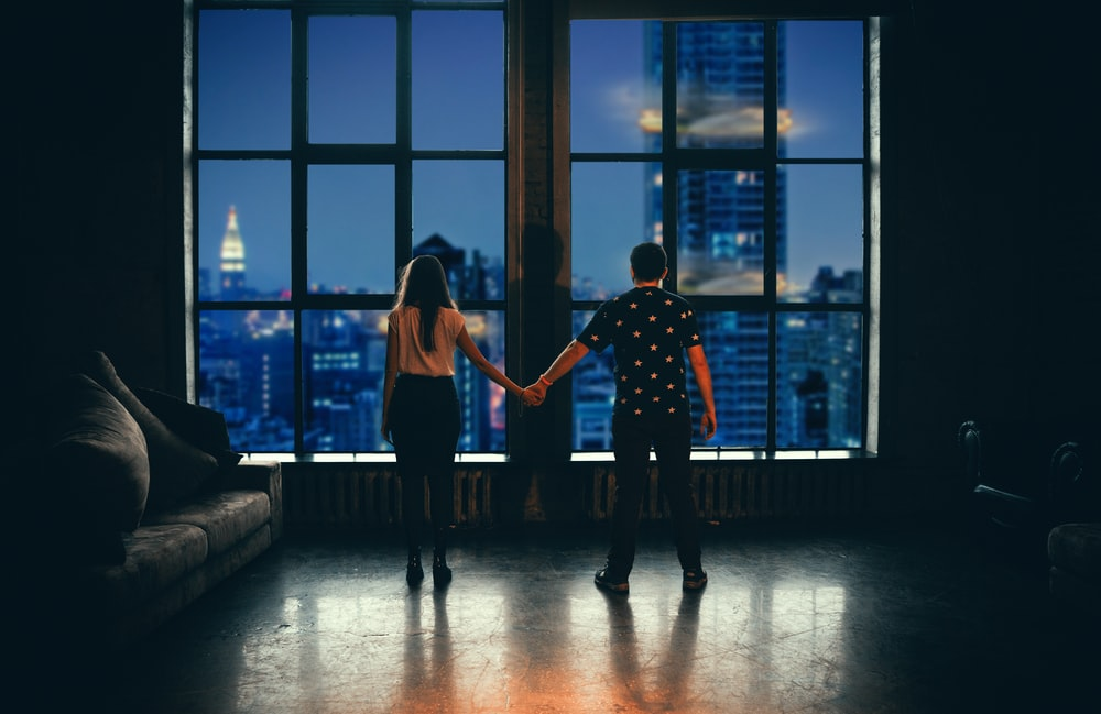 man and woman holding hands in front of glass window