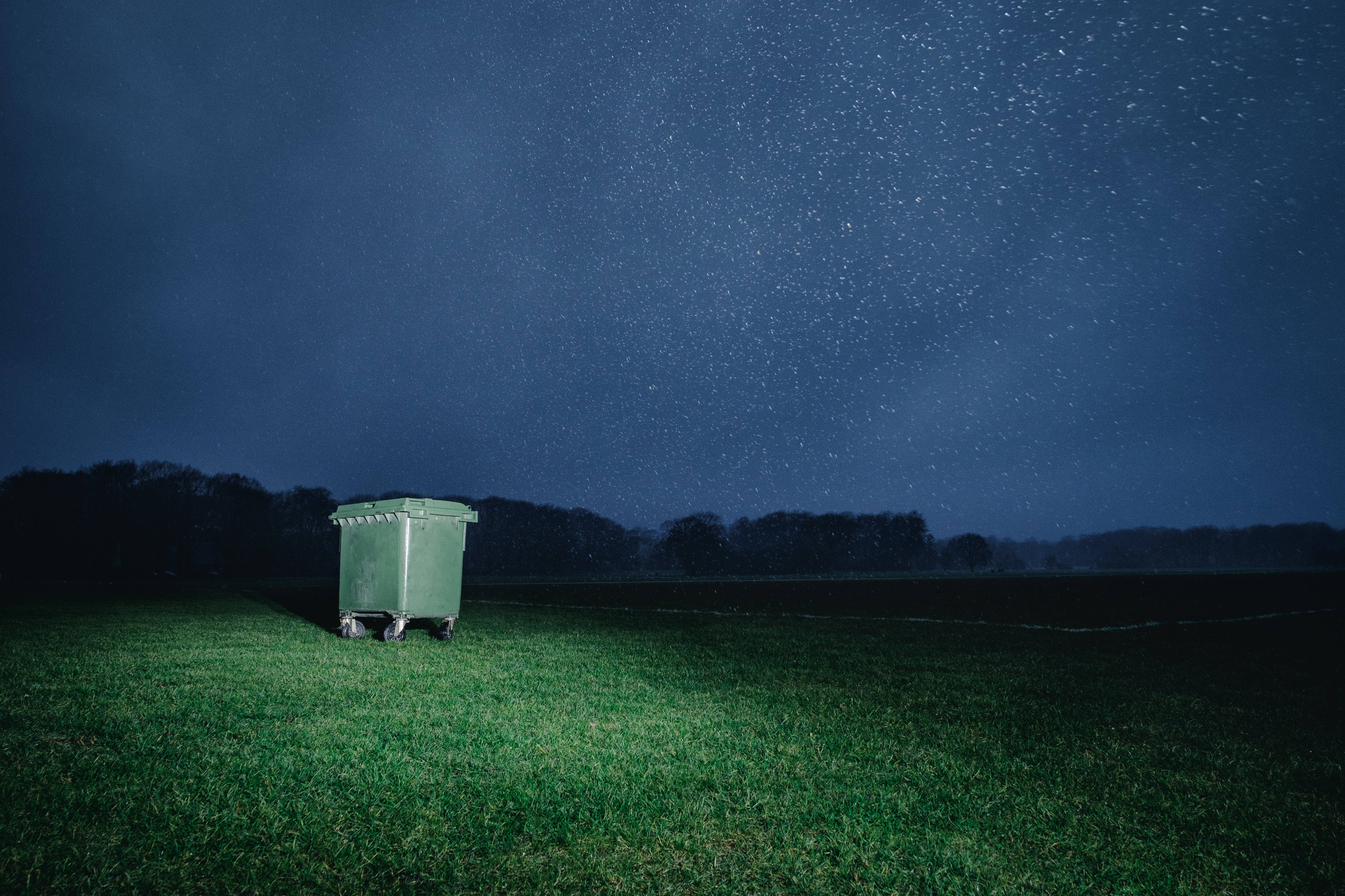 A garbage can sitting in a field under a starry night sky.
