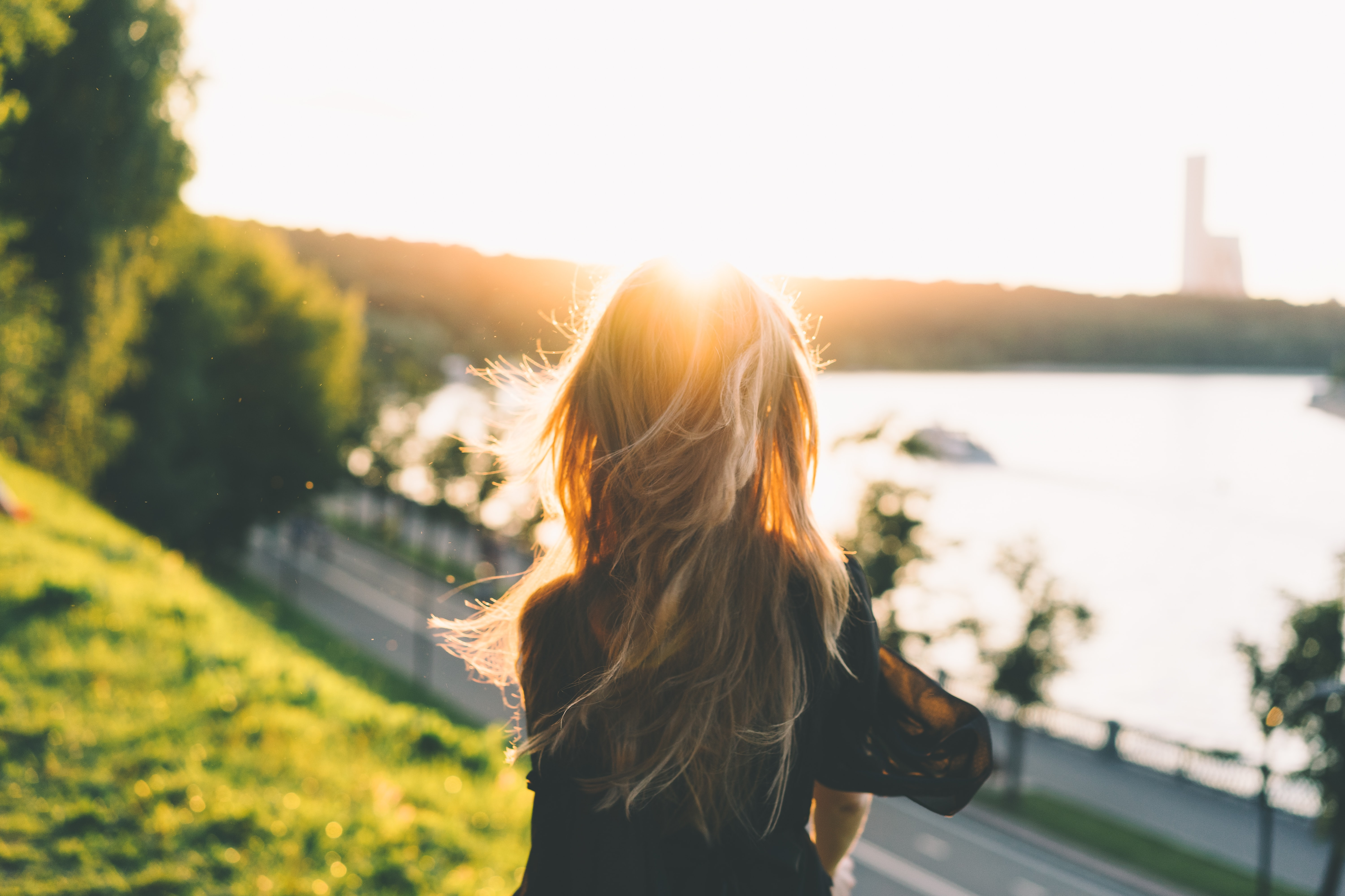A woman standing on a hill, looking towards the sun.