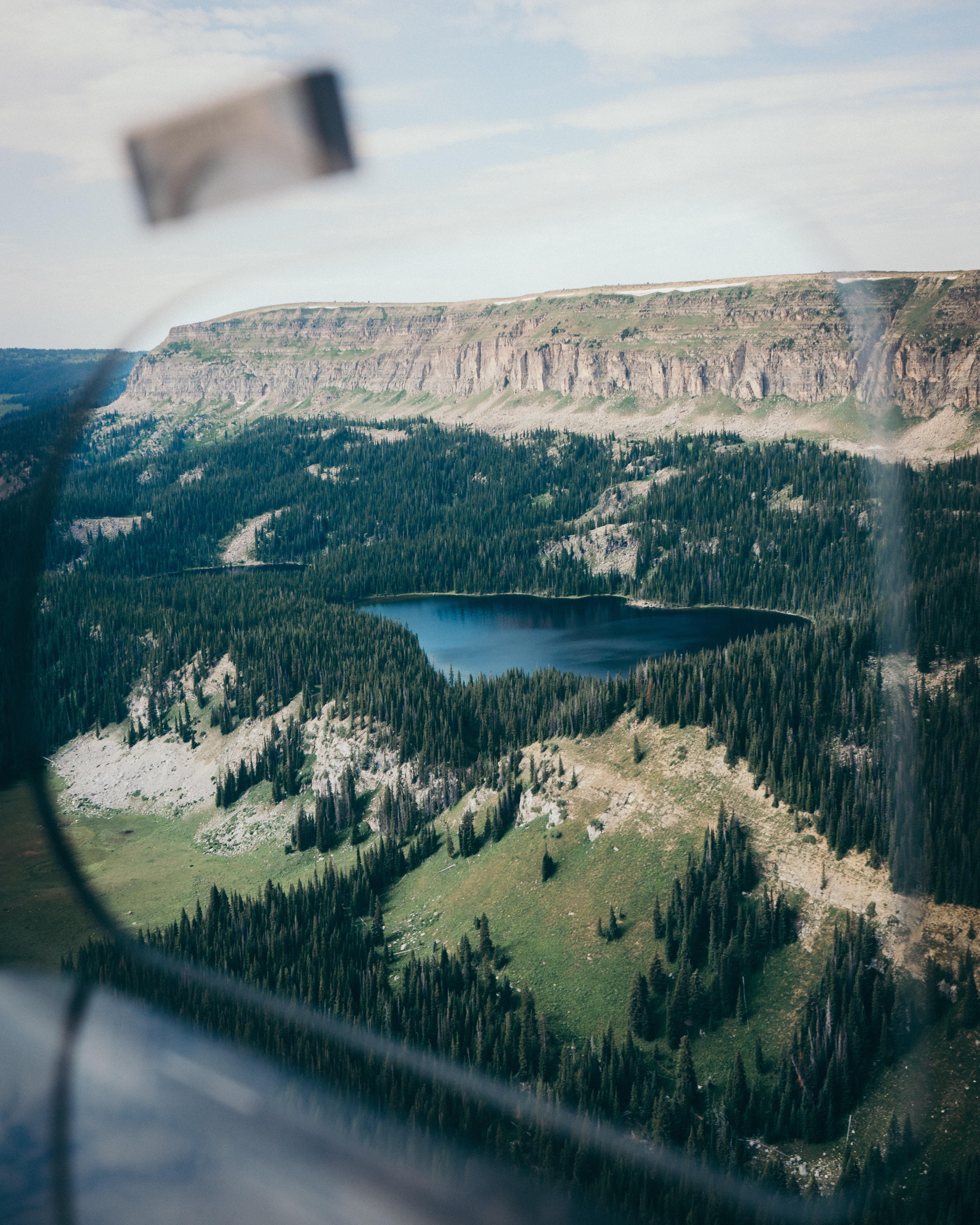 A high view of a tree-lined lake near a mountain plateau