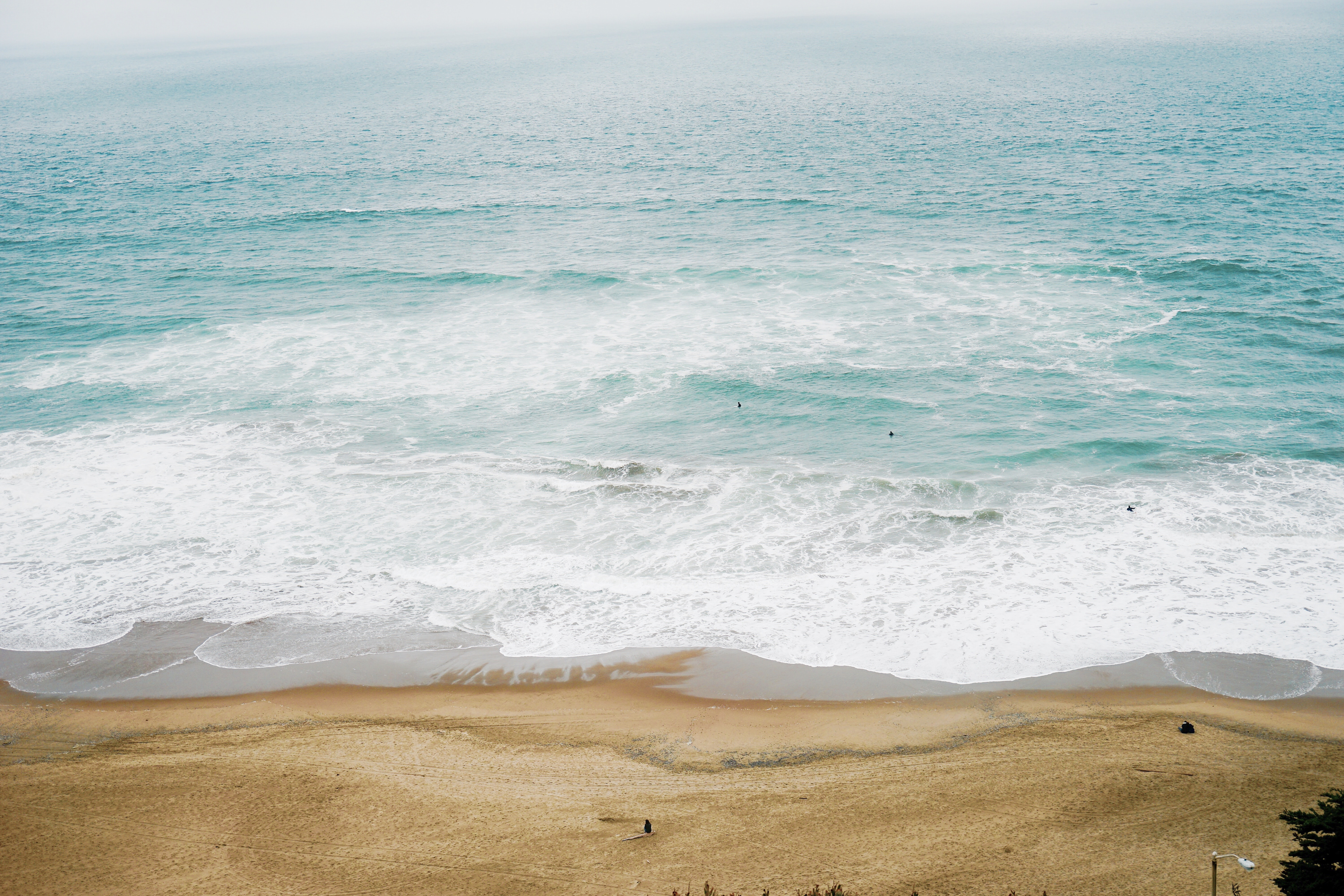 Drone view of the ocean washing on the sand beach at Ocean Beach