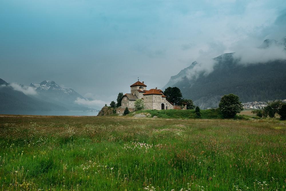 beige concrete house on grass fields