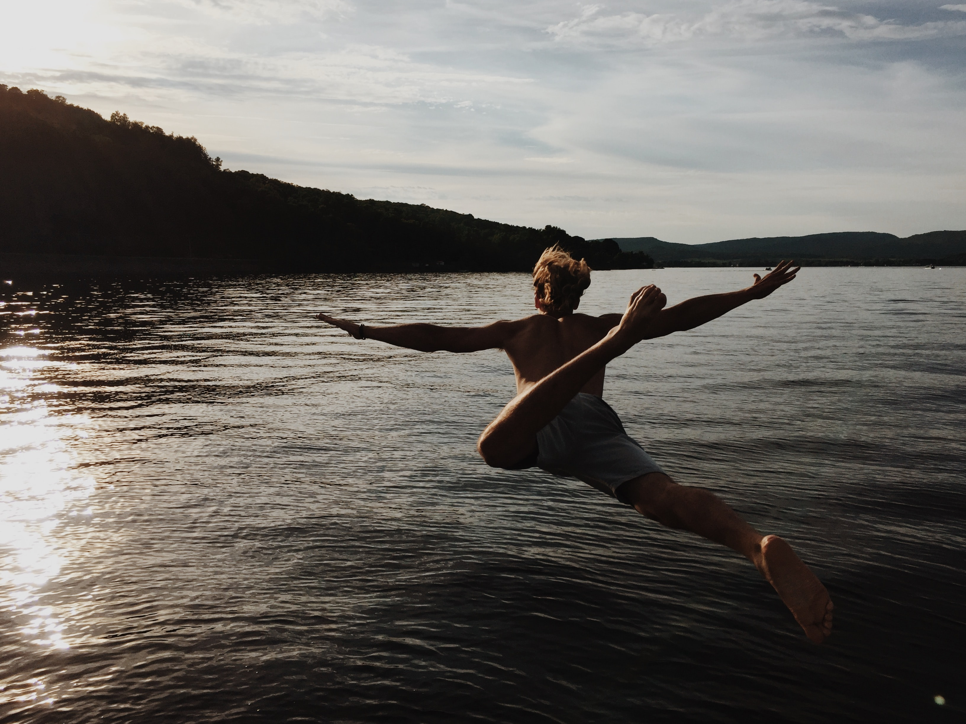 A man in swimwear jumping into the lake during sunset