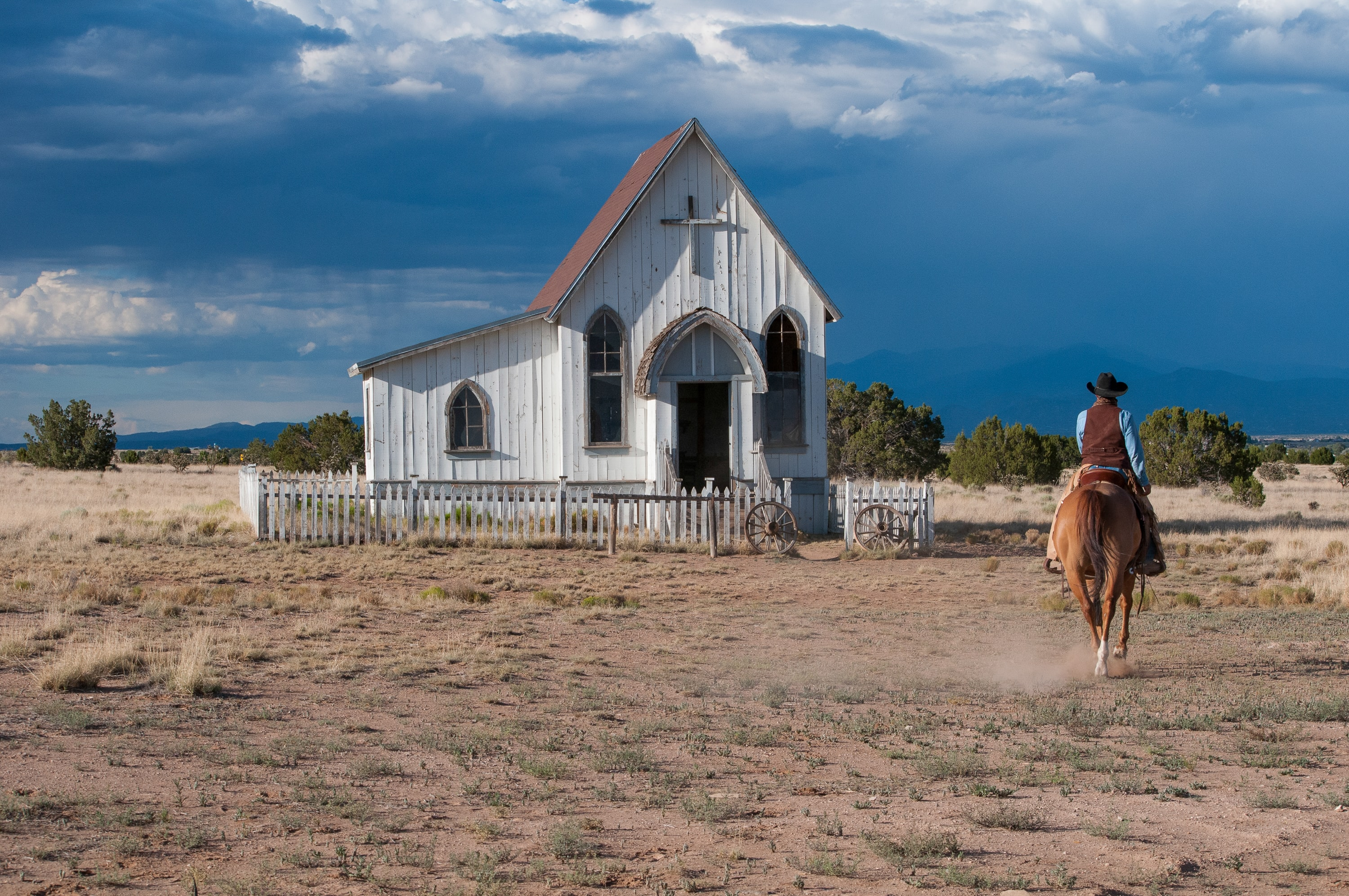 A man in a cowboy hat riding a horse near a wooden chapel in the middle of arid plains