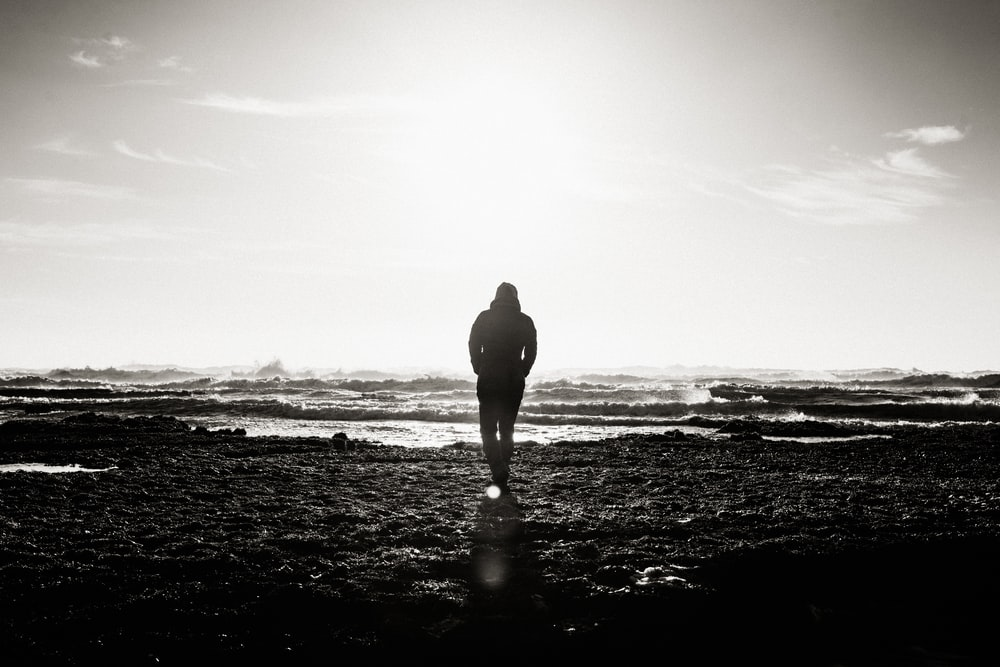 Black and white shot of person walking towards sea water on shore with clouds in sky