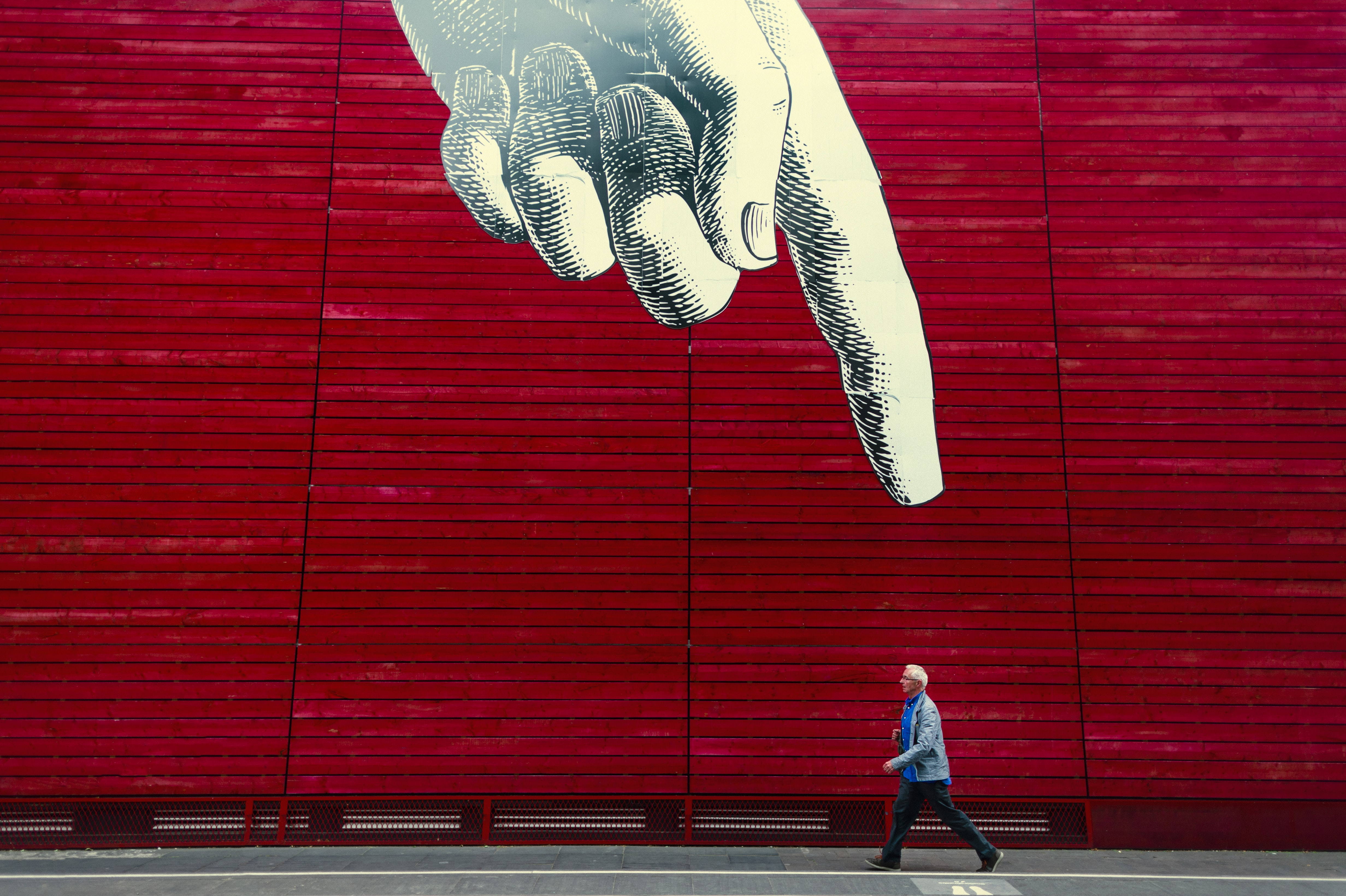 A person walking by a wall painting of a realistic hand with its index finger pointing down.