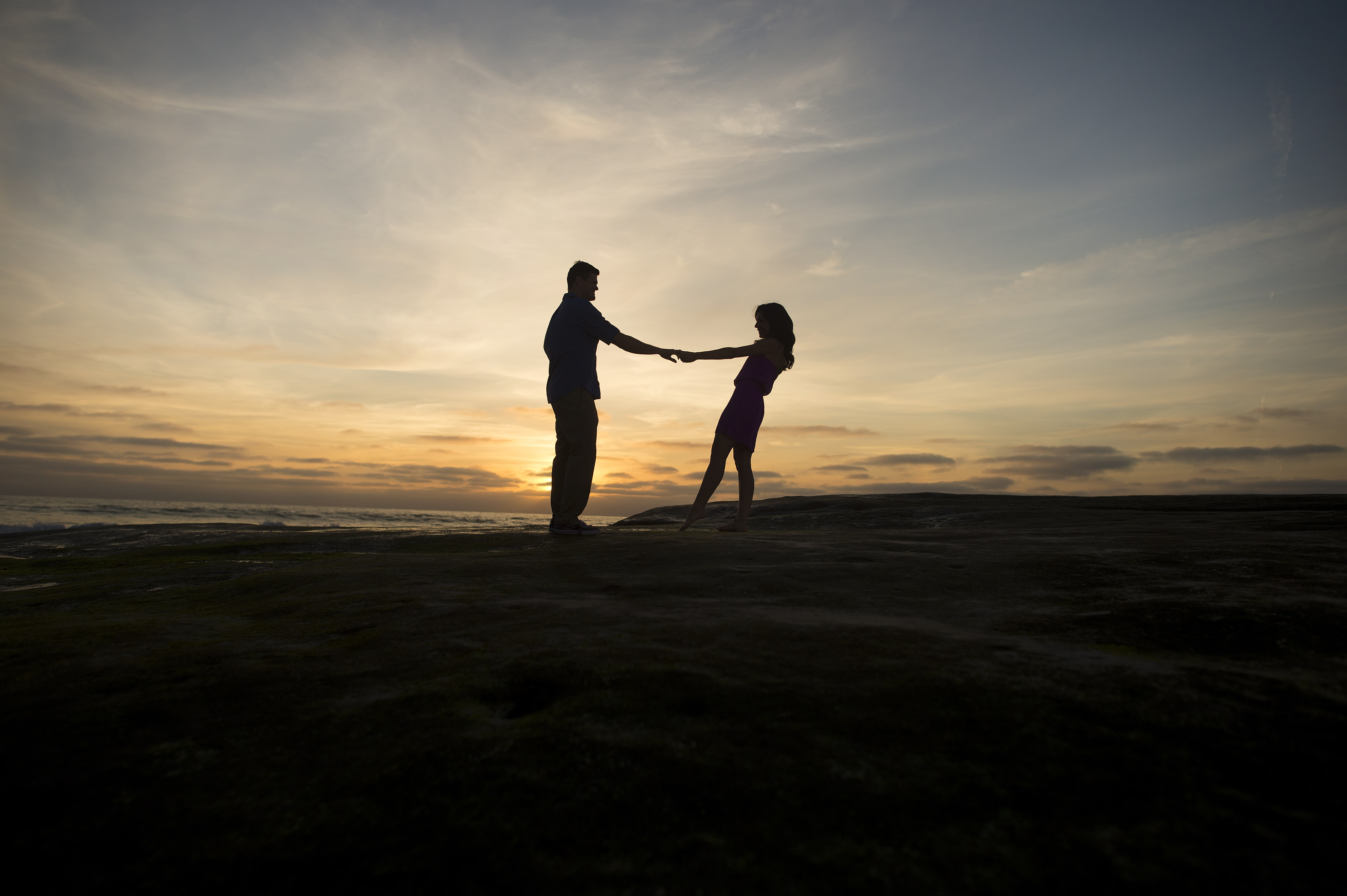 Couple spins round holding hands, silhouetted against setting the sun