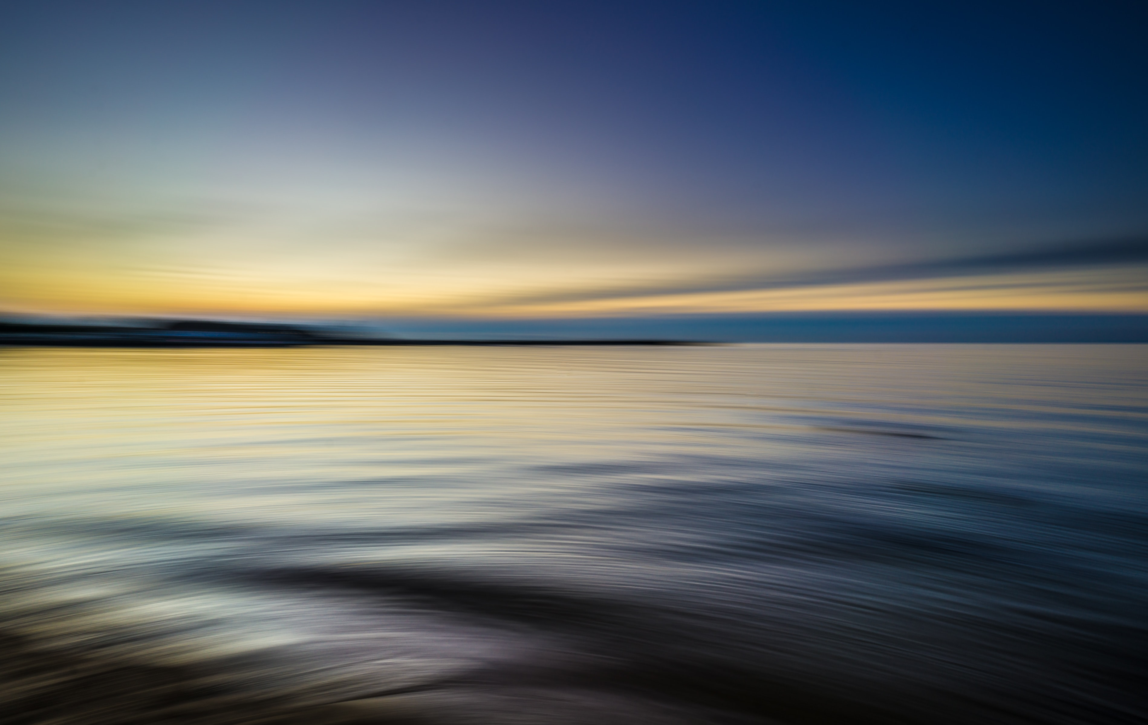 Tranquil rippling waters reflect a blue and yellow sky at sunset