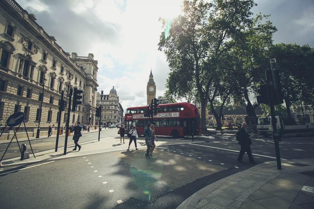 group of people walking on London road beside double deaker bus