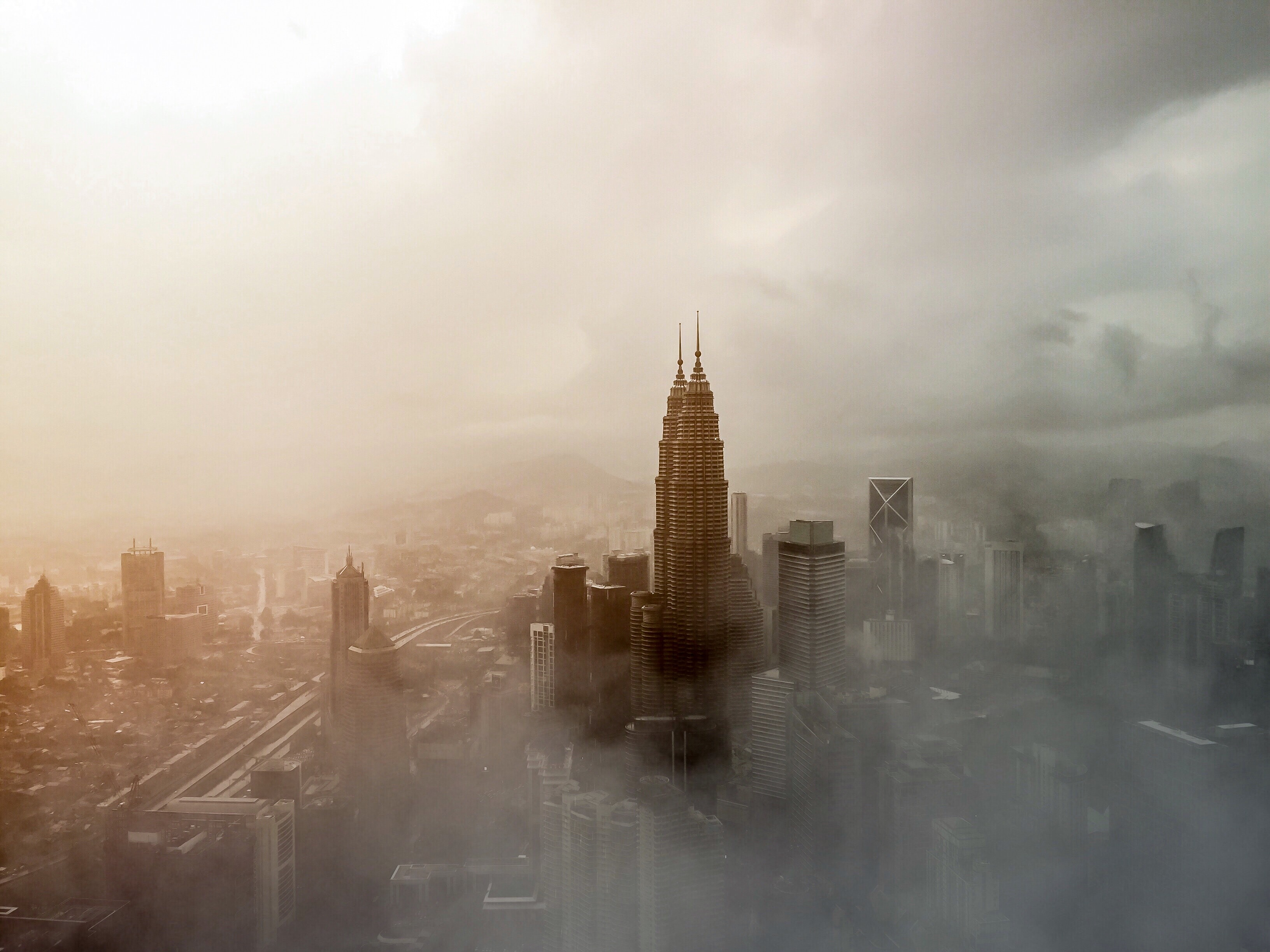 Tall skyscrapers in Kuala Lumpur wreathed in a dense fog