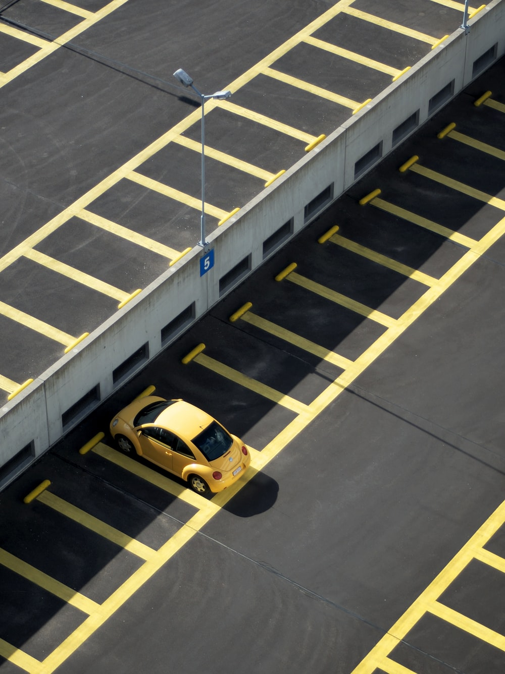 yellow coupe on parking lot at daytime