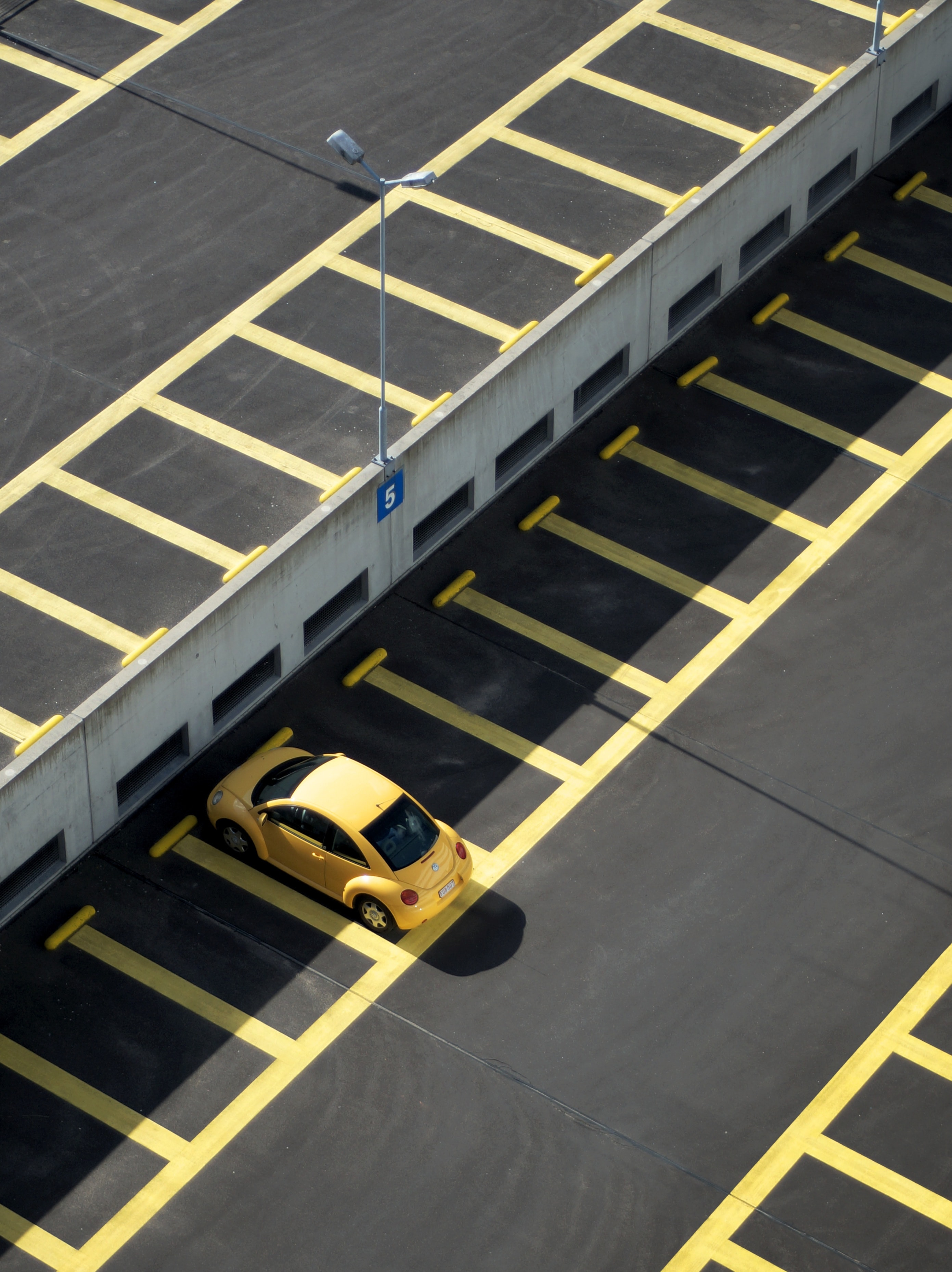 Drone shot of a solitary yellow Volkswagen Beetle in a parking garage with yellow lines.