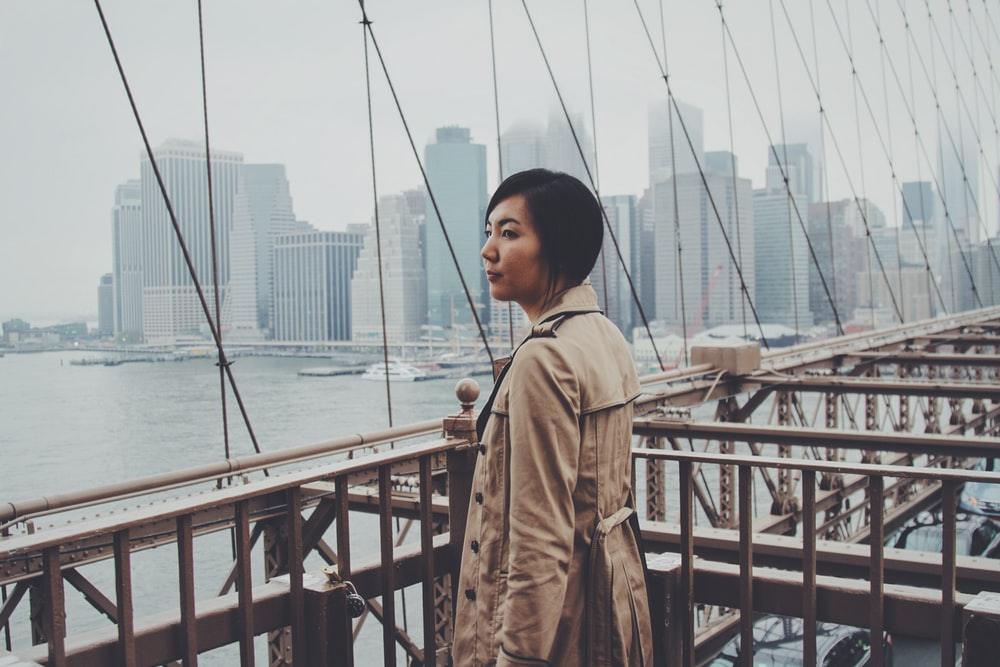 woman standing on bridge railings at daytime