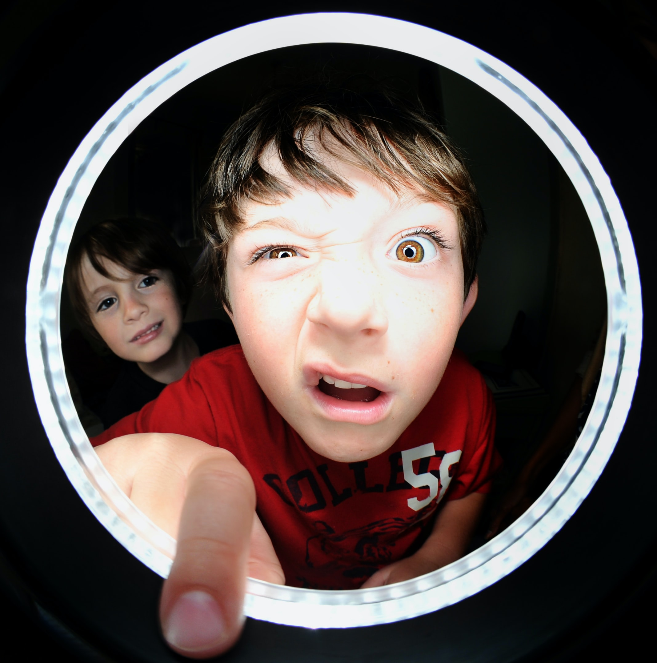 A little boy making a funny face while sticking his finger through a peephole.