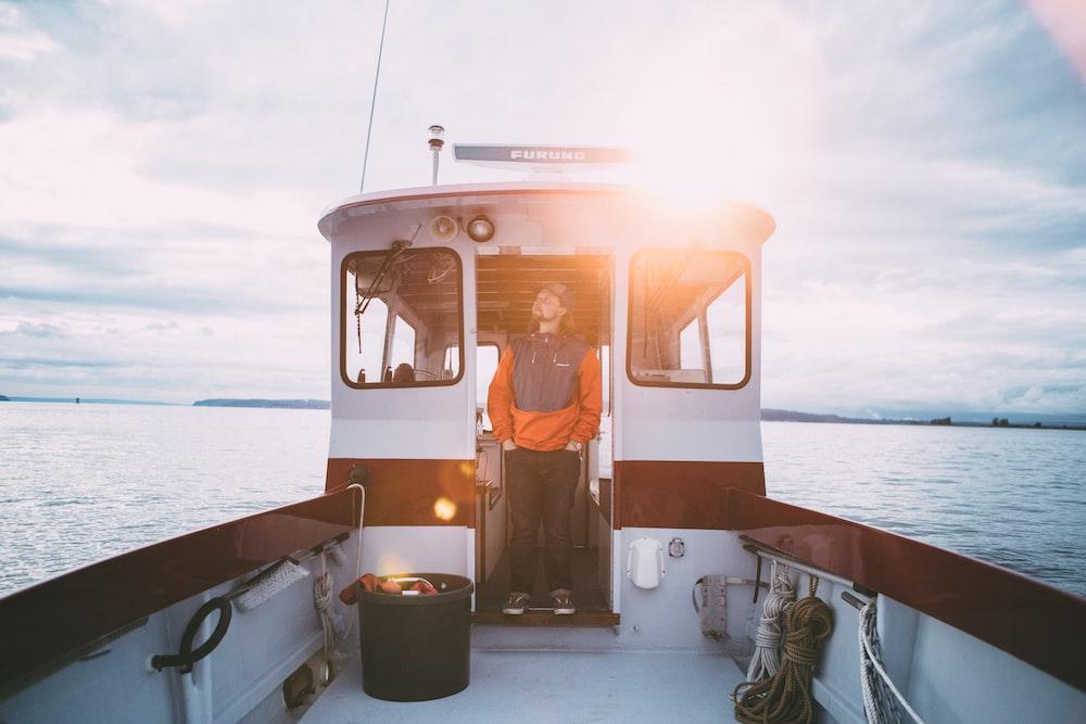 man standing inside sailboat