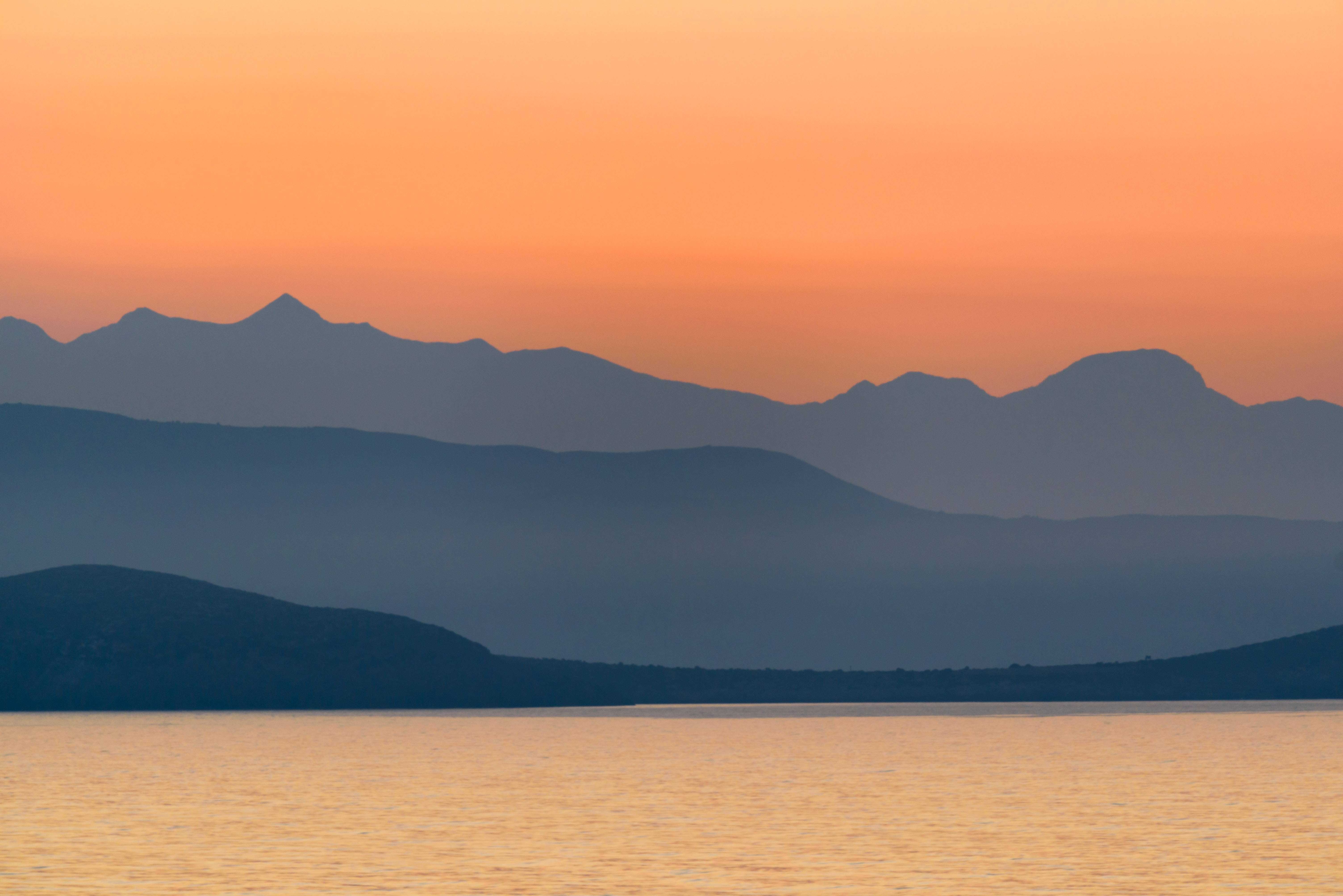 An orange sky at sunset over the tranquil water and Peloponnese mountains