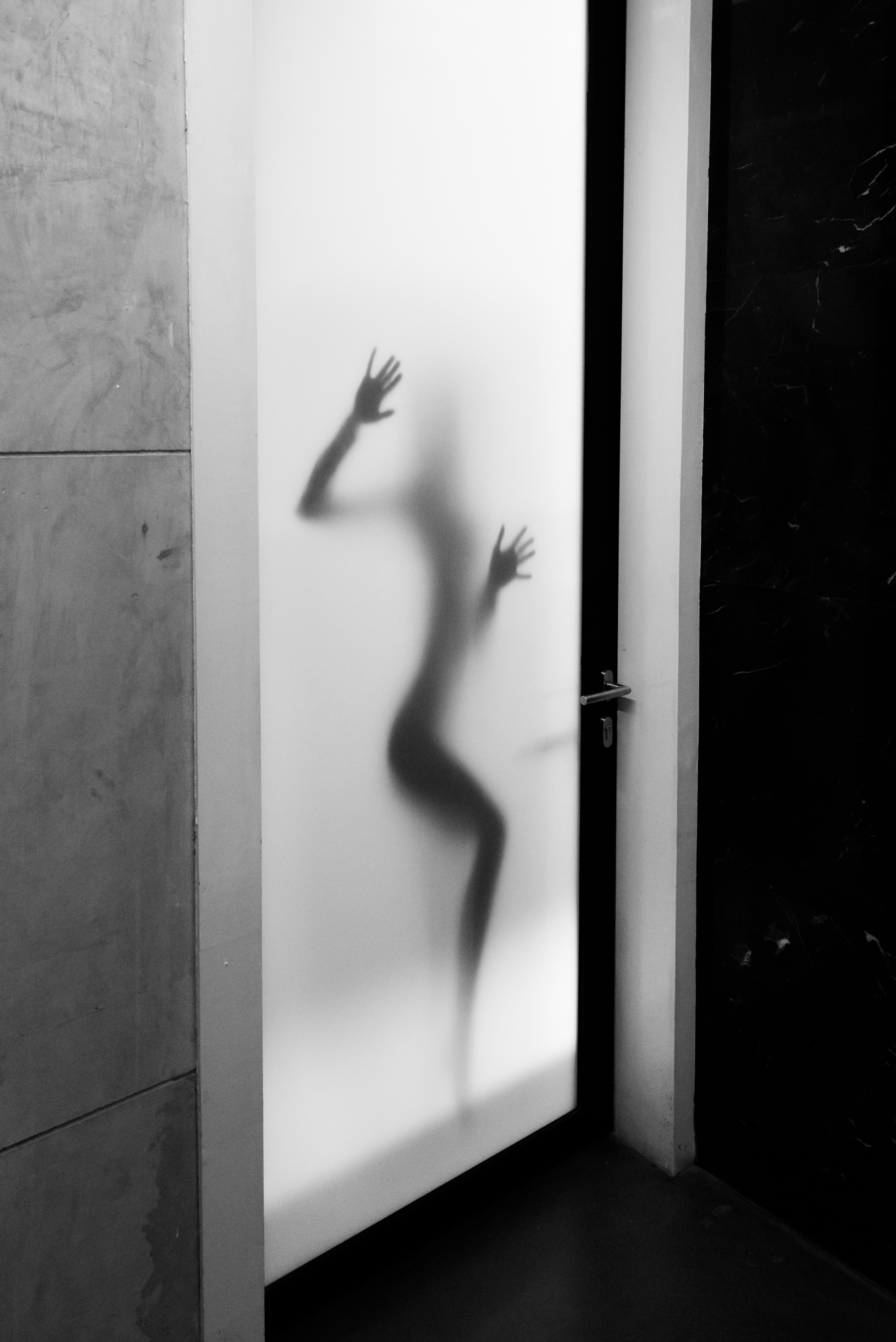 The silhouette of a woman behind frosted glass