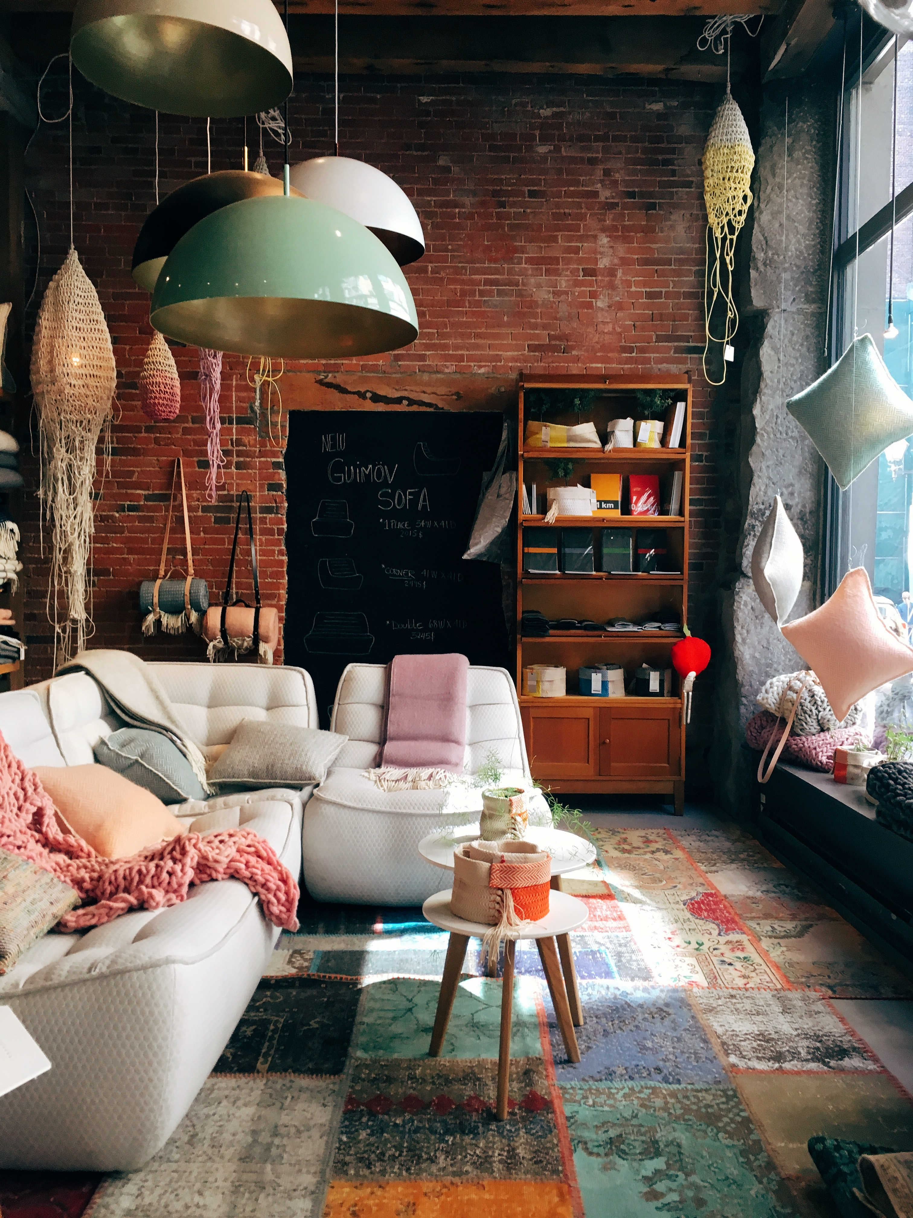 A living room having a brick wall, glass windows and containing a white sofa with throw pillows in Canada.