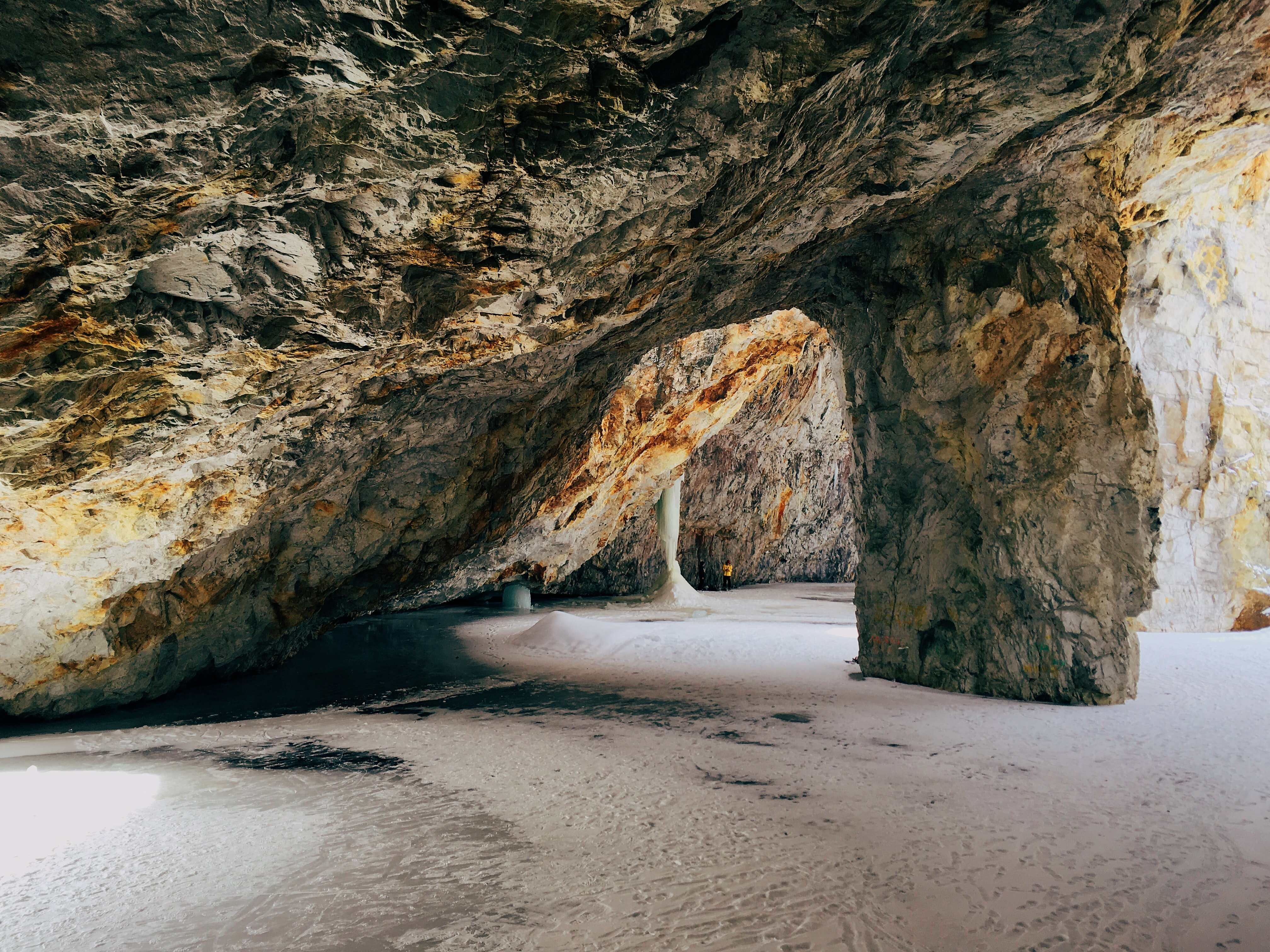 Open rock cave on a sand beach