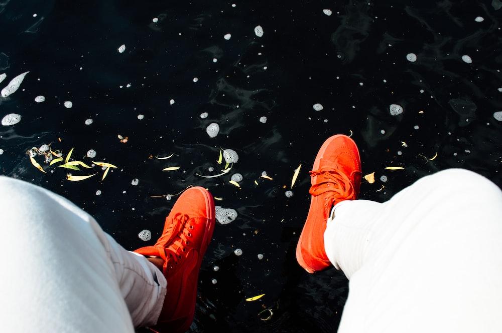 person wearing orange sneakers sitting near water