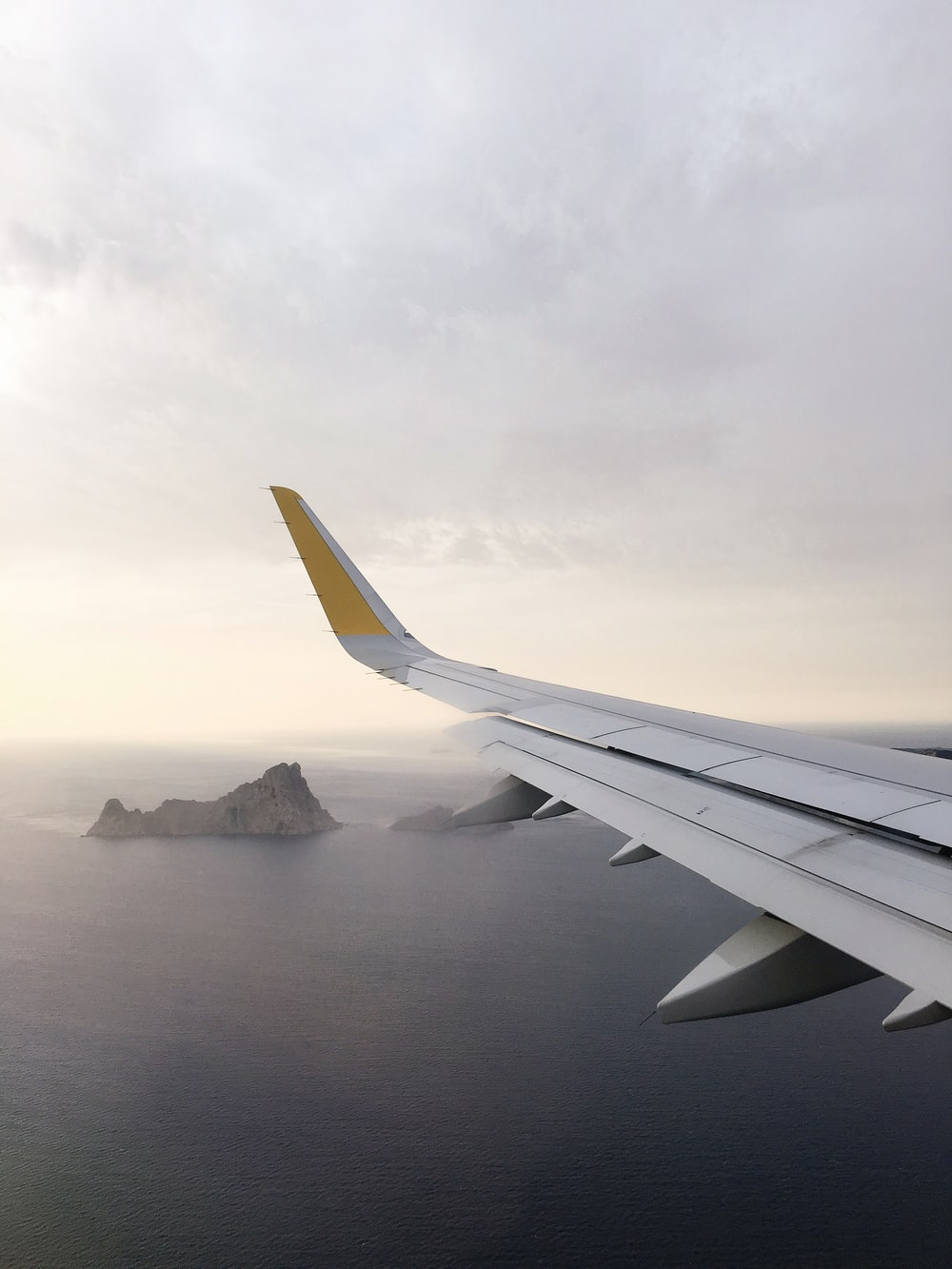 airplane wing above body of water during daytime