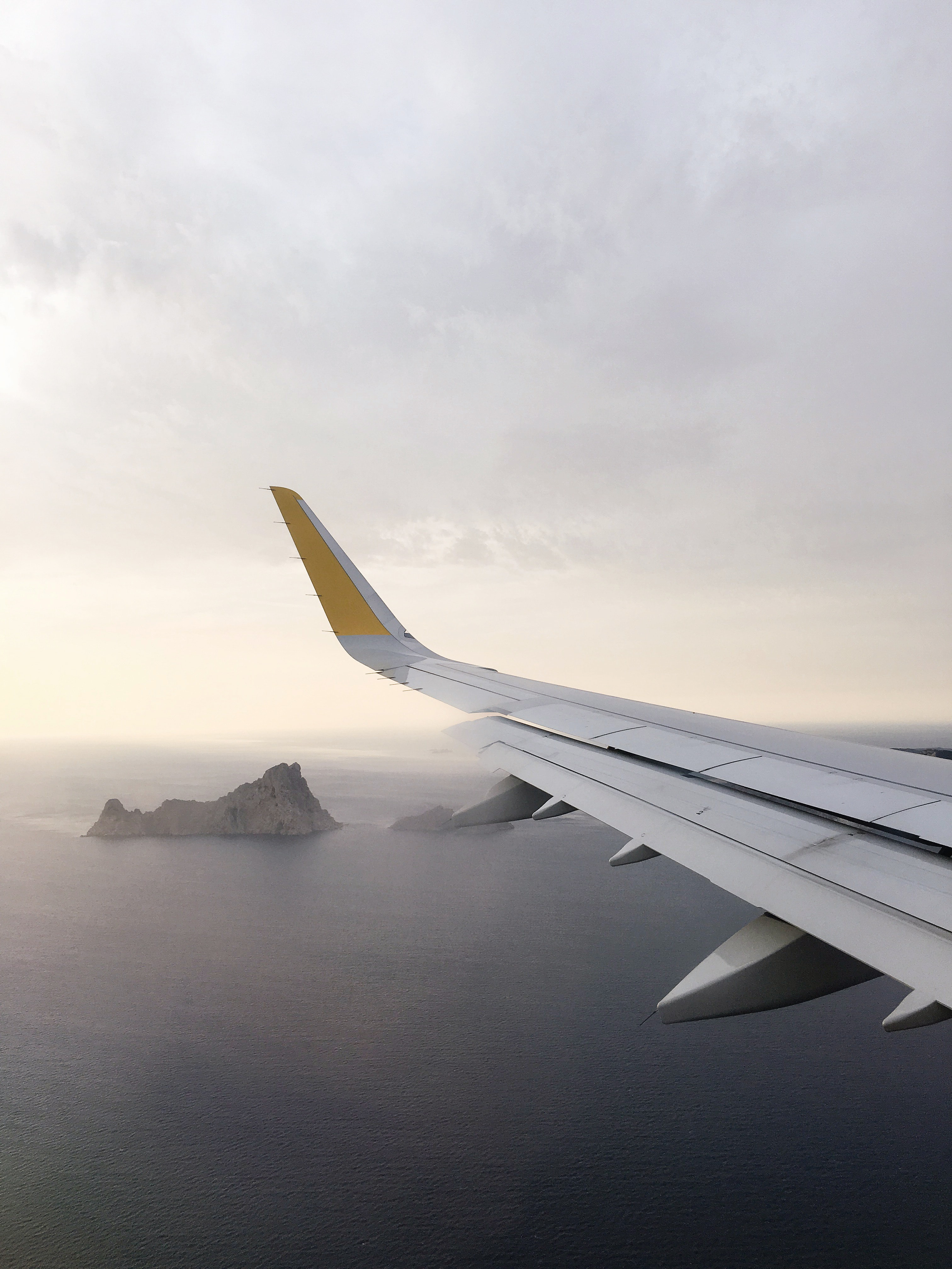 A view from an airplane window on the surface of the ocean with rocky islands jutting out of the water
